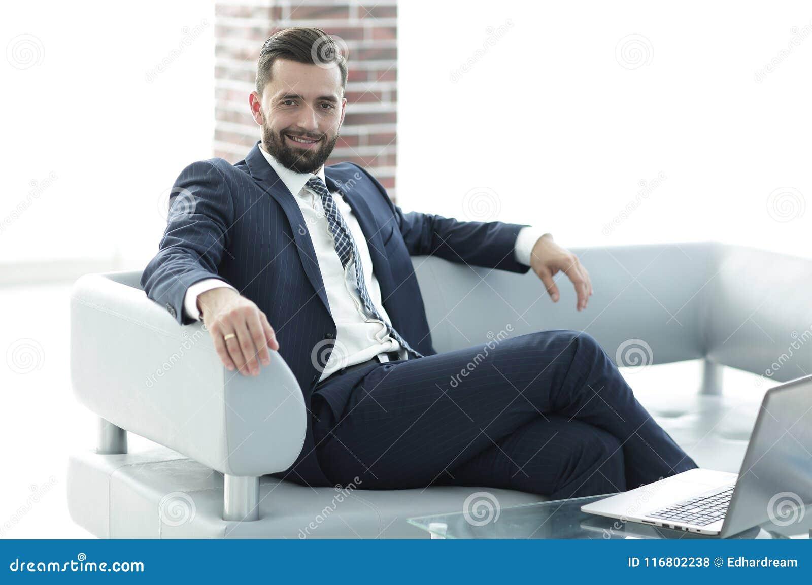 Ritratto di riuscito uomo d affari che si siede nell ingresso dell ufficio