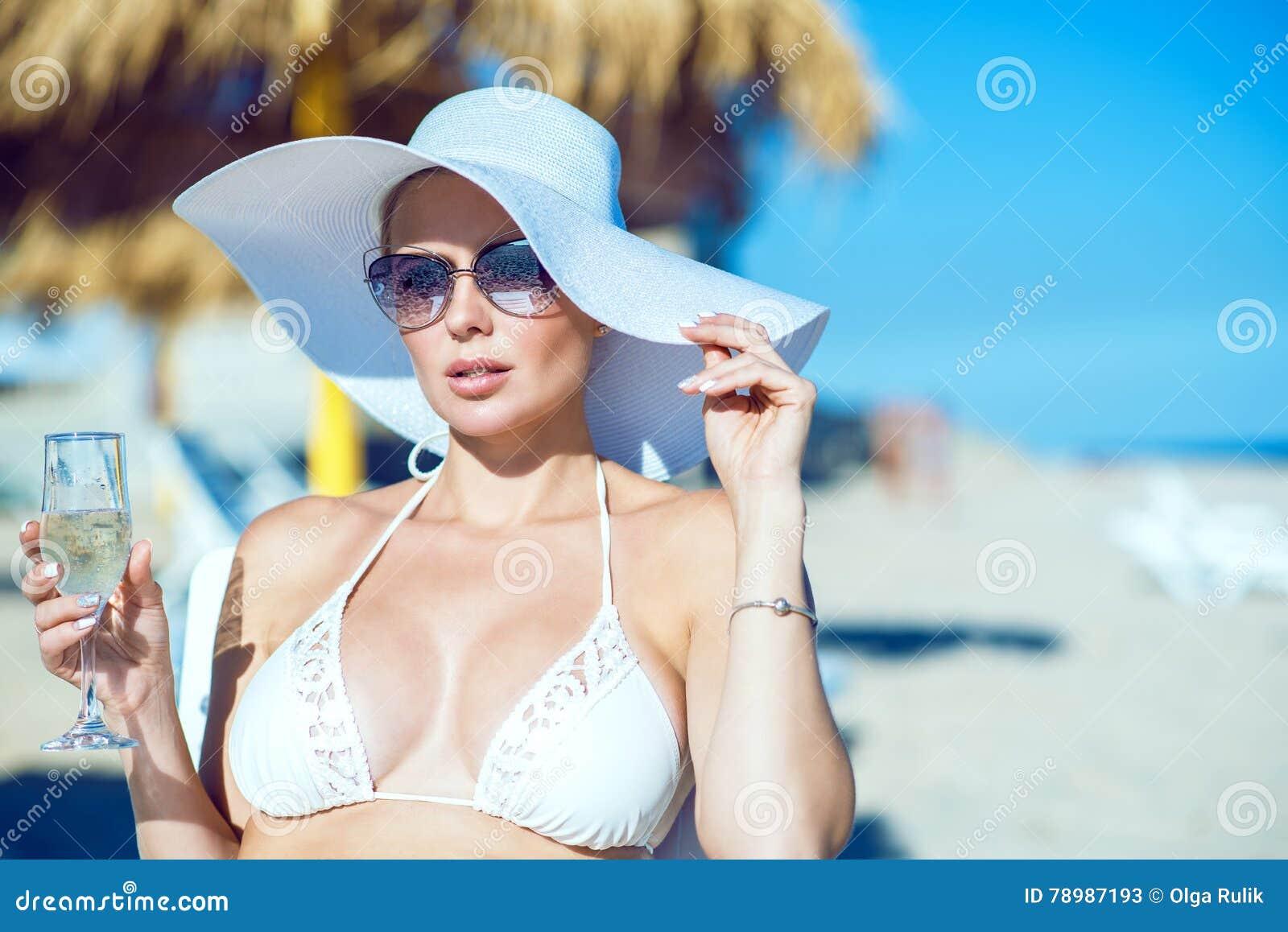 Ritratto di signora affascinante in reggiseno bianco di nuoto, cappello a tesa larga ed occhiali da sole sedentesi sulle chaise l
