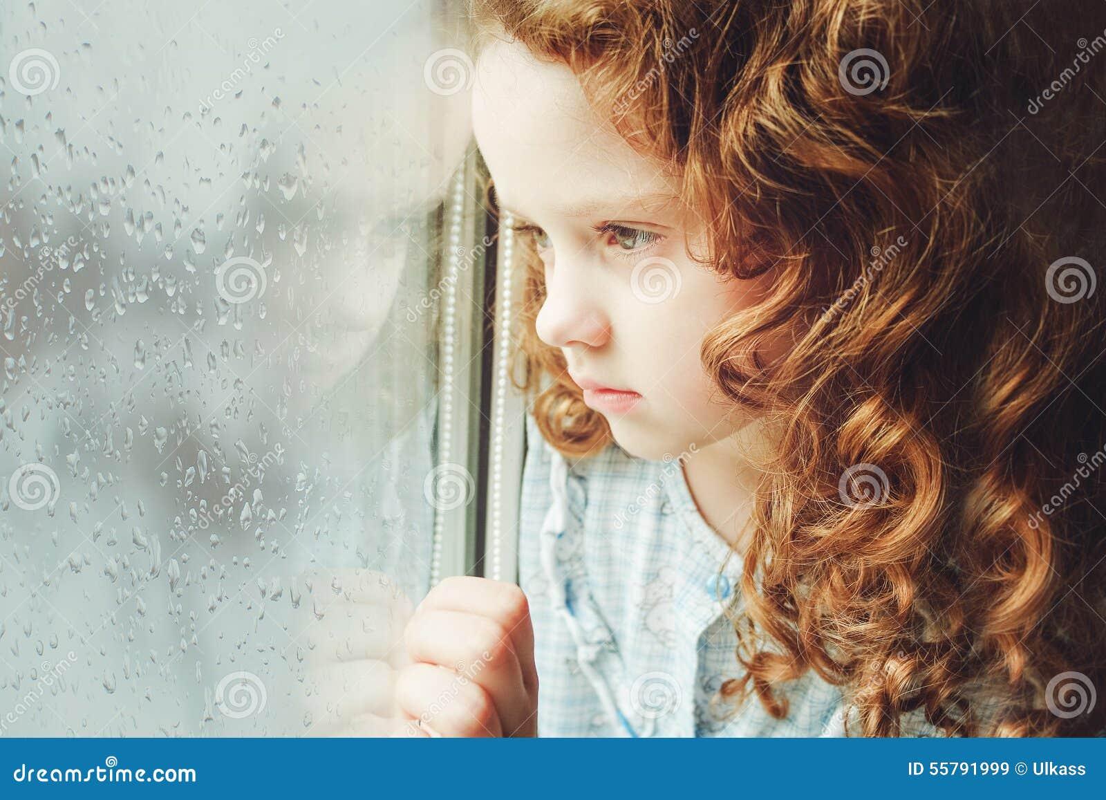 Ritratto di un bambino triste che guarda fuori la finestra Tonalità della foto