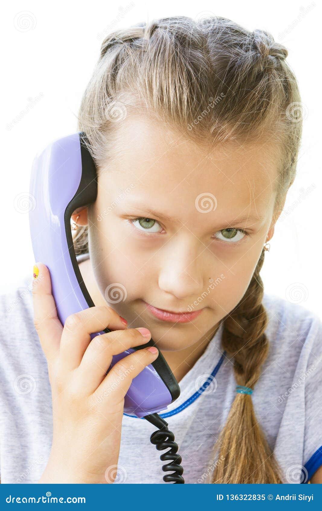 Ritratto di un girlie con un microtelefono di vecchio telefono su un fondo bianco