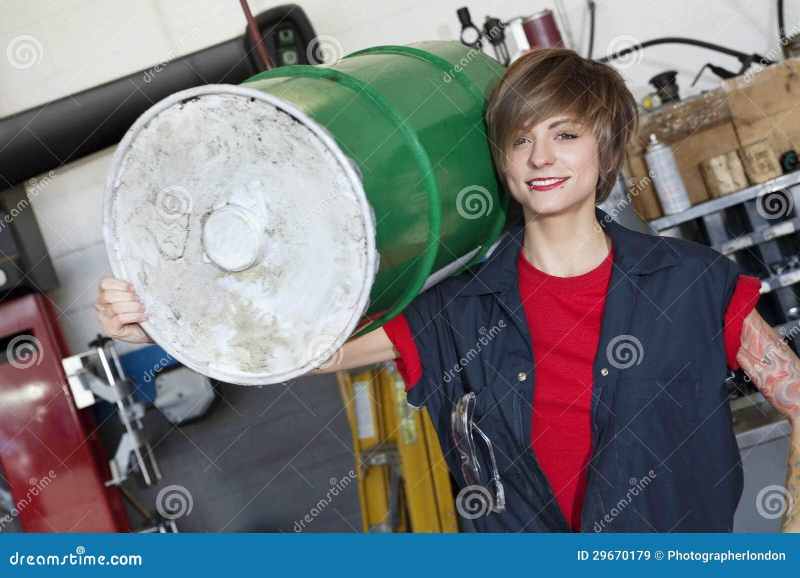 Ritratto di un tamburo dell olio di trasporto del giovane meccanico femminile felice sulla spalla nell officina dell automobile
