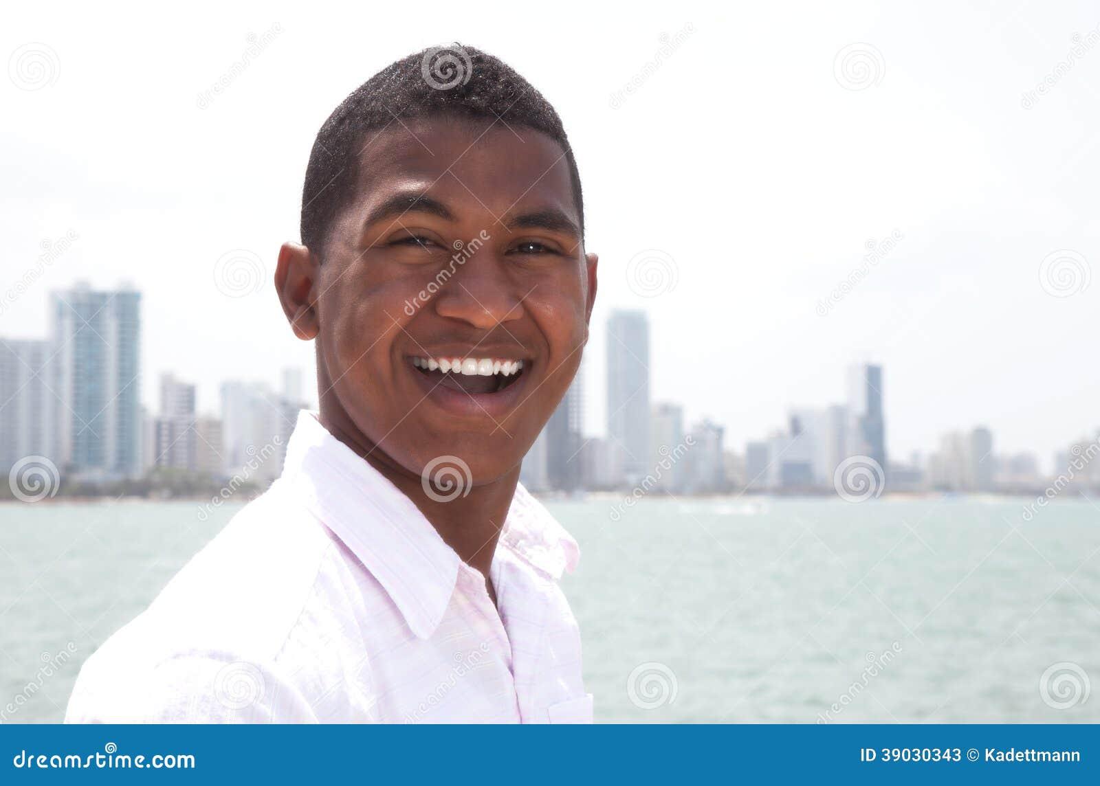 Ritratto di un tipo di risata alla spiaggia con orizzonte