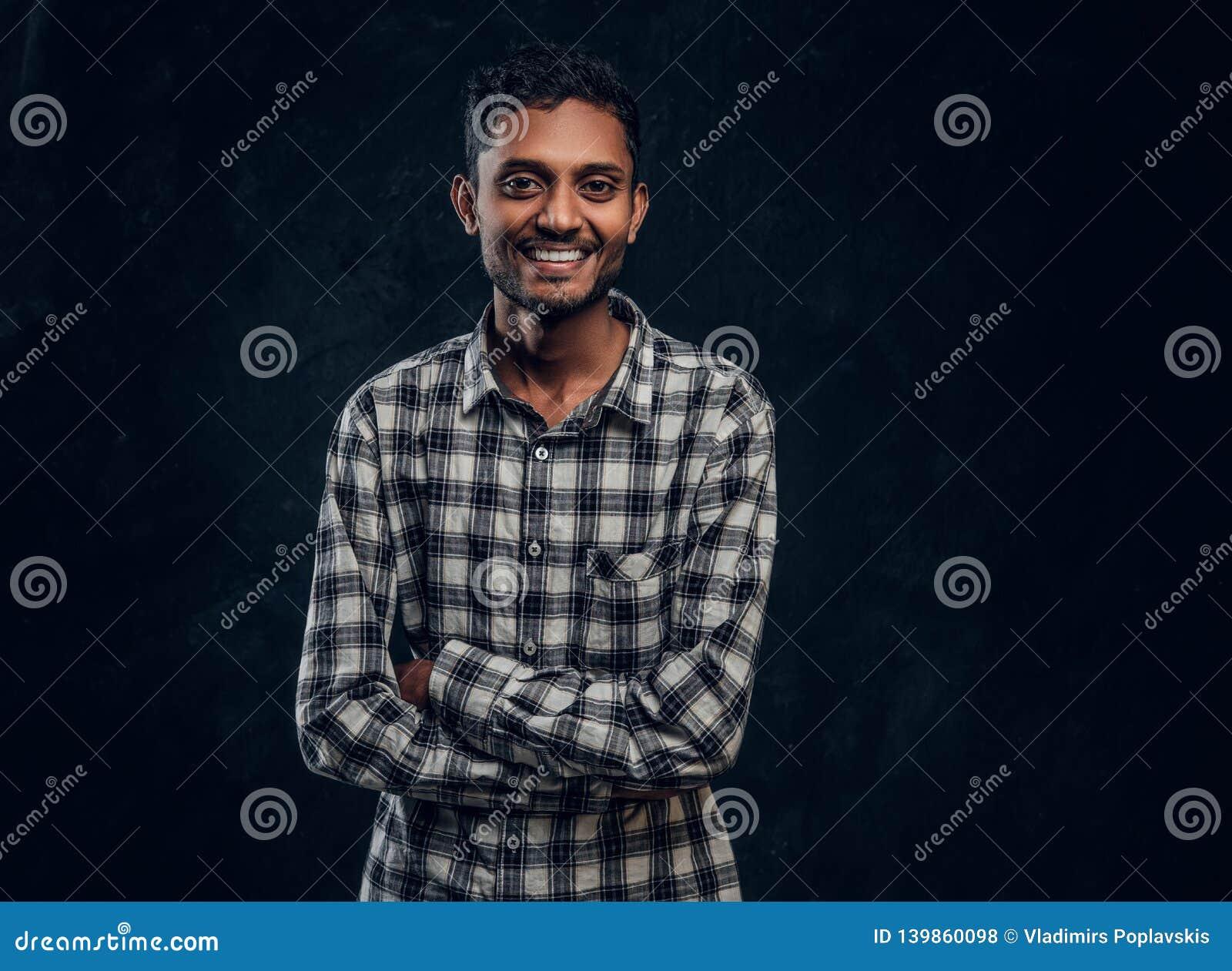 Ritratto di un tipo indiano sorridente che porta una camicia a quadretti che posa con le sue armi attraversate e che esamina la m