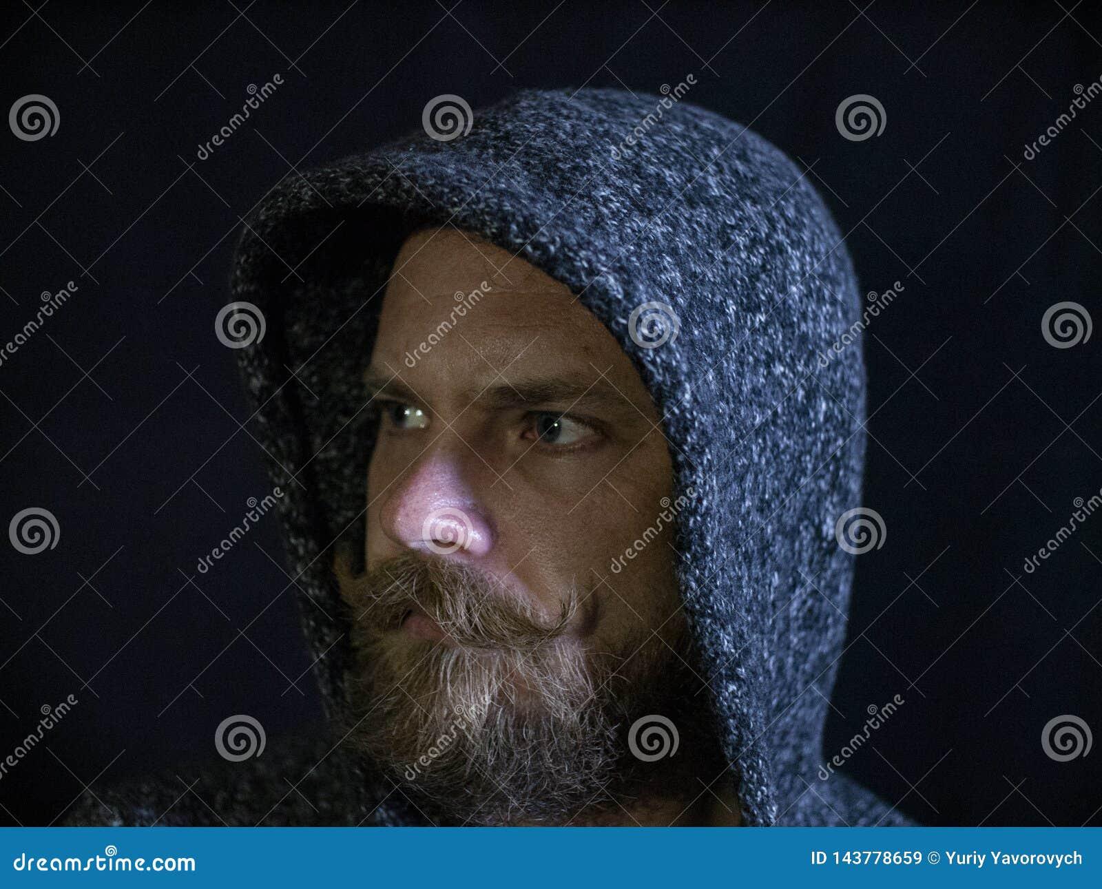 Ritratto di un uomo con una barba e dei baffi nel cappuccio con un fronte serio su un fondo nero