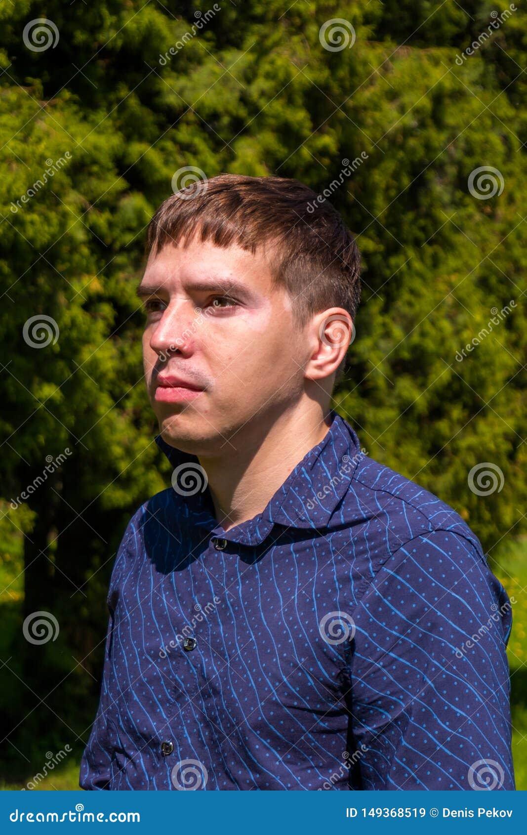 Ritratto di un uomo nell esterno diritto della camicia blu in parco
