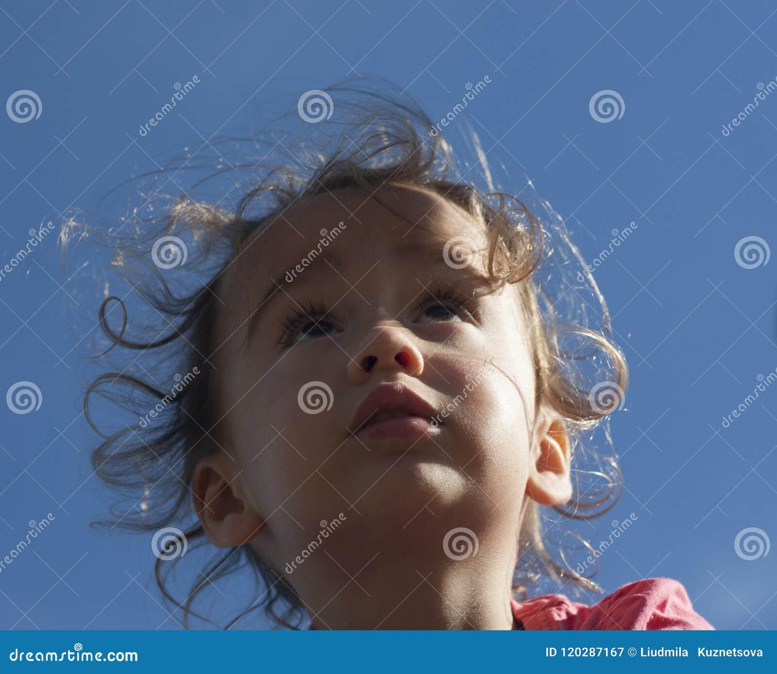 Ritratto di una bambina che cerca contro il cielo