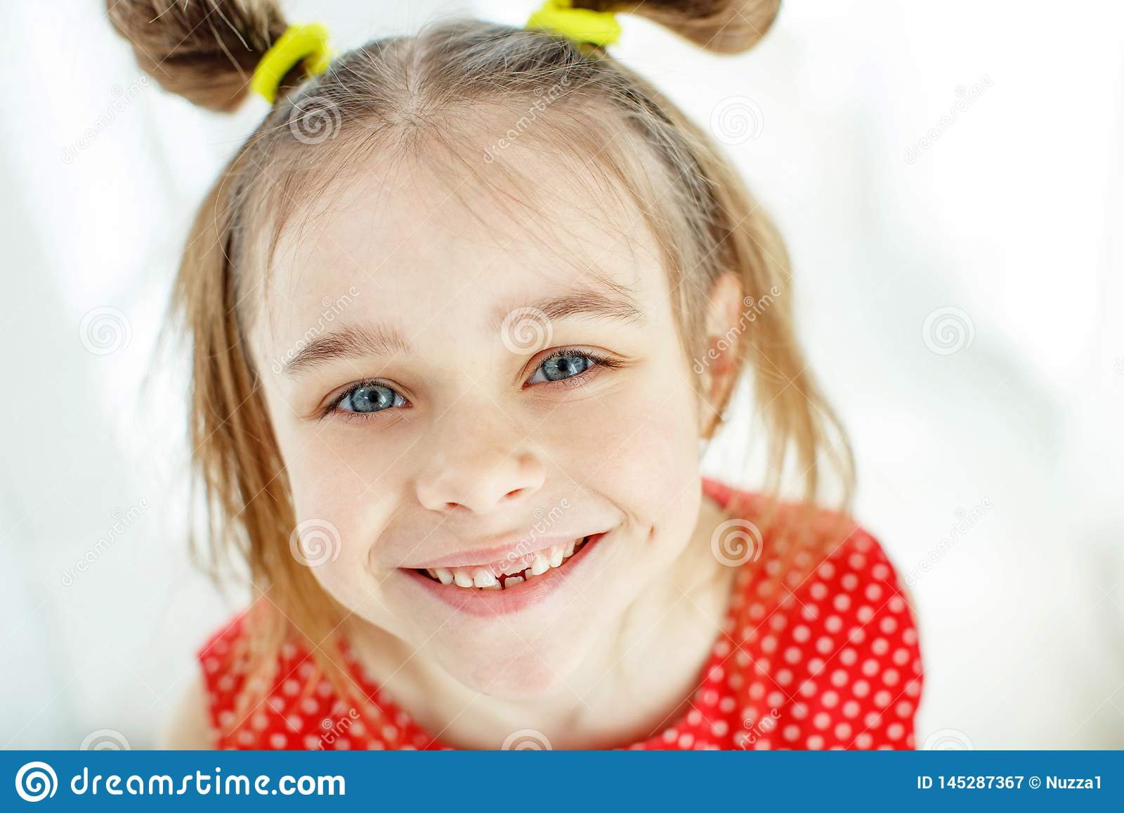 Ritratto di una bambina divertente senza un dente anteriore