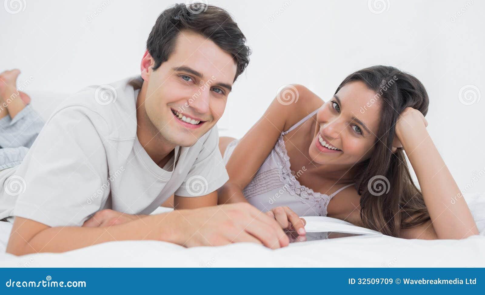 Ritratto di una coppia facendo uso di una compressa che si trova a letto immagine stock - Letto che si chiude ...