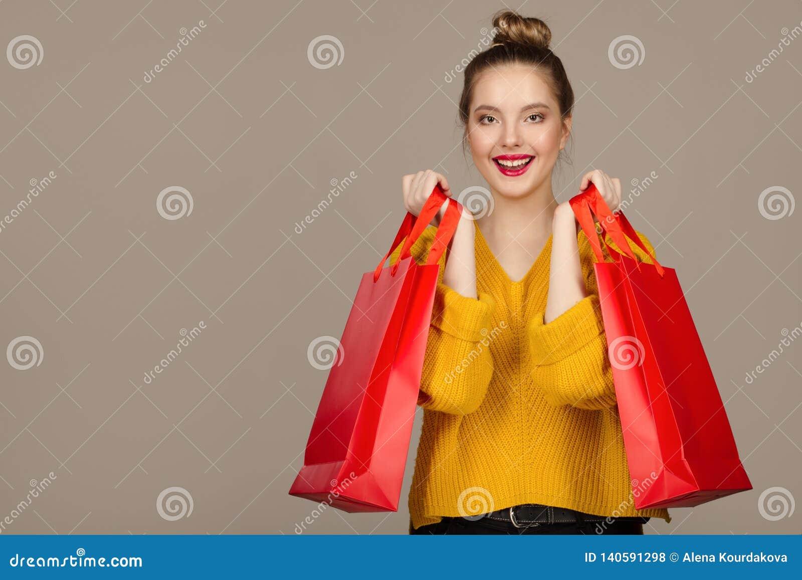 Ritratto di una donna allegra felice che tiene i sacchetti della spesa rossi