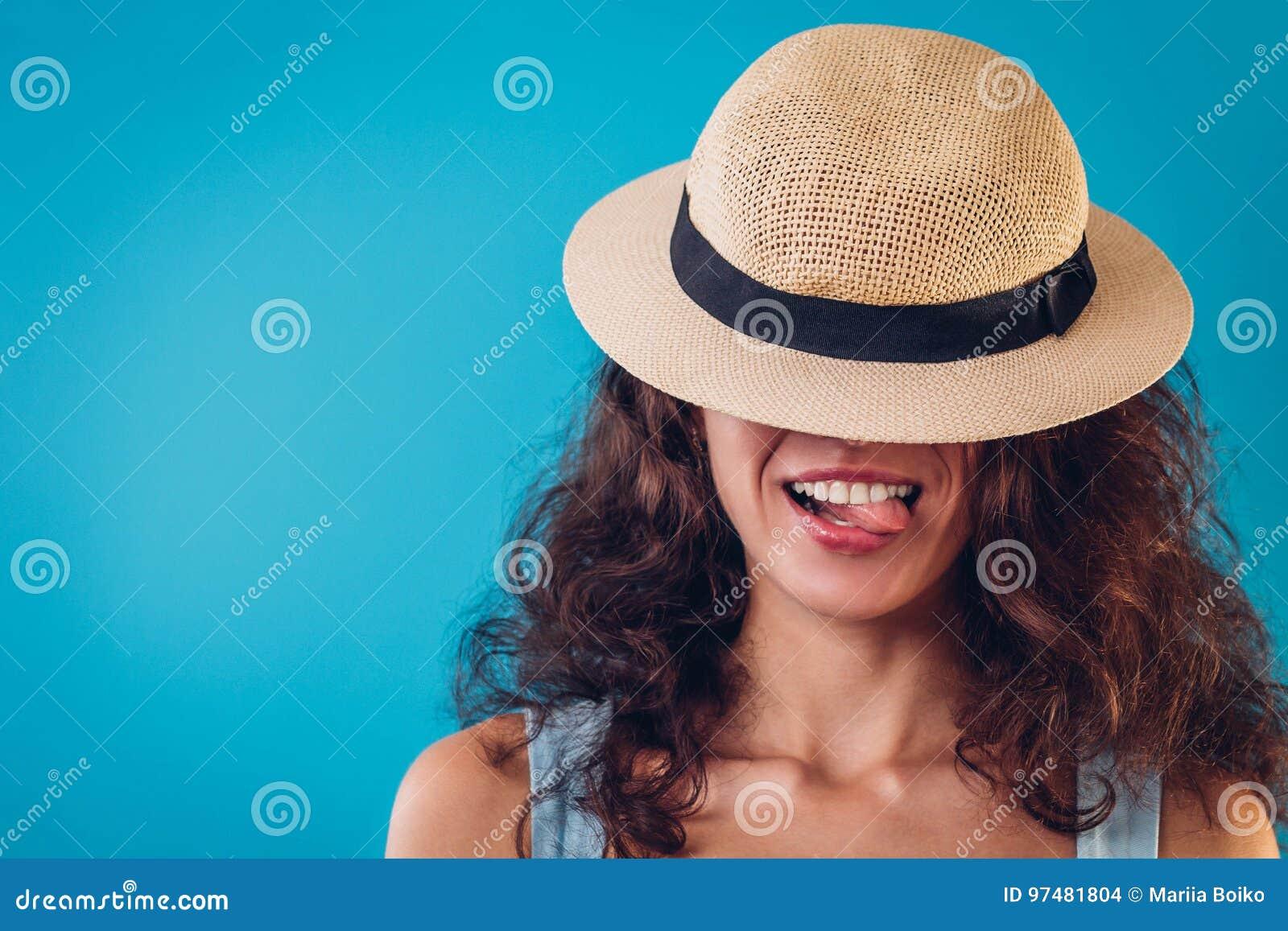 Ritratto di una donna graziosa che si nasconde sotto il cappello e che mostra lingua