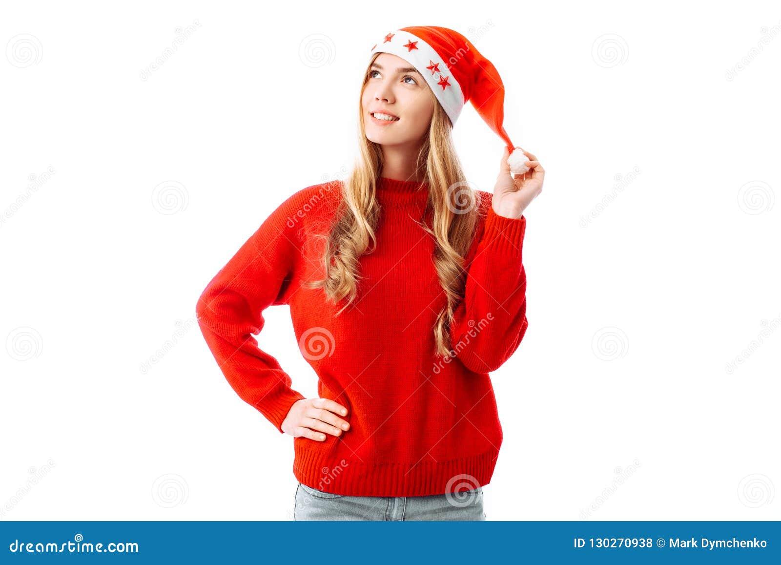 Ritratto di una donna sorridente che porta un maglione e un cappello rossi di Santa Claus, stante e guardante al lato, isolato su