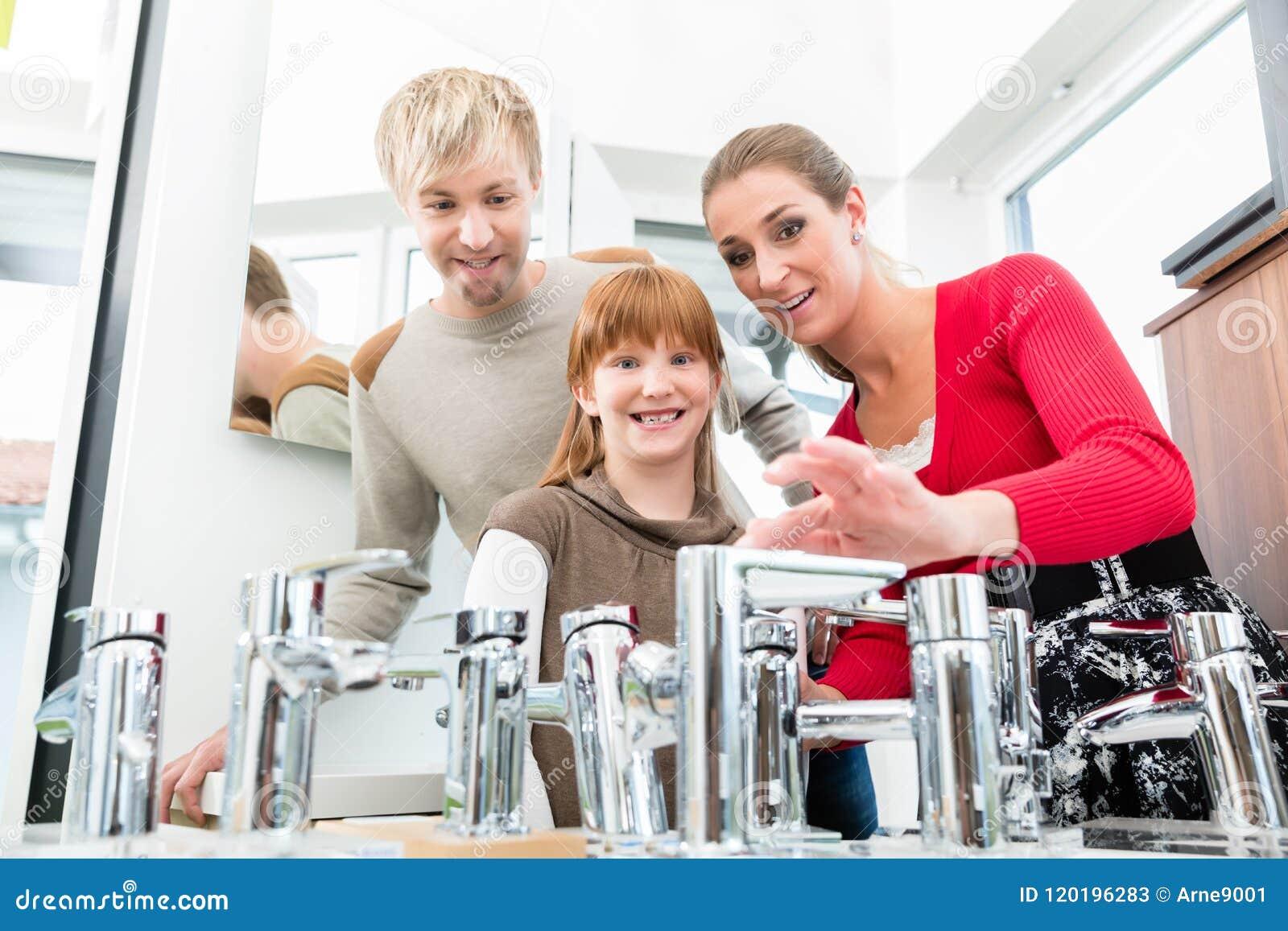 Ritratto di una famiglia felice che cerca un nuovo rubinetto del lavandino del bagno