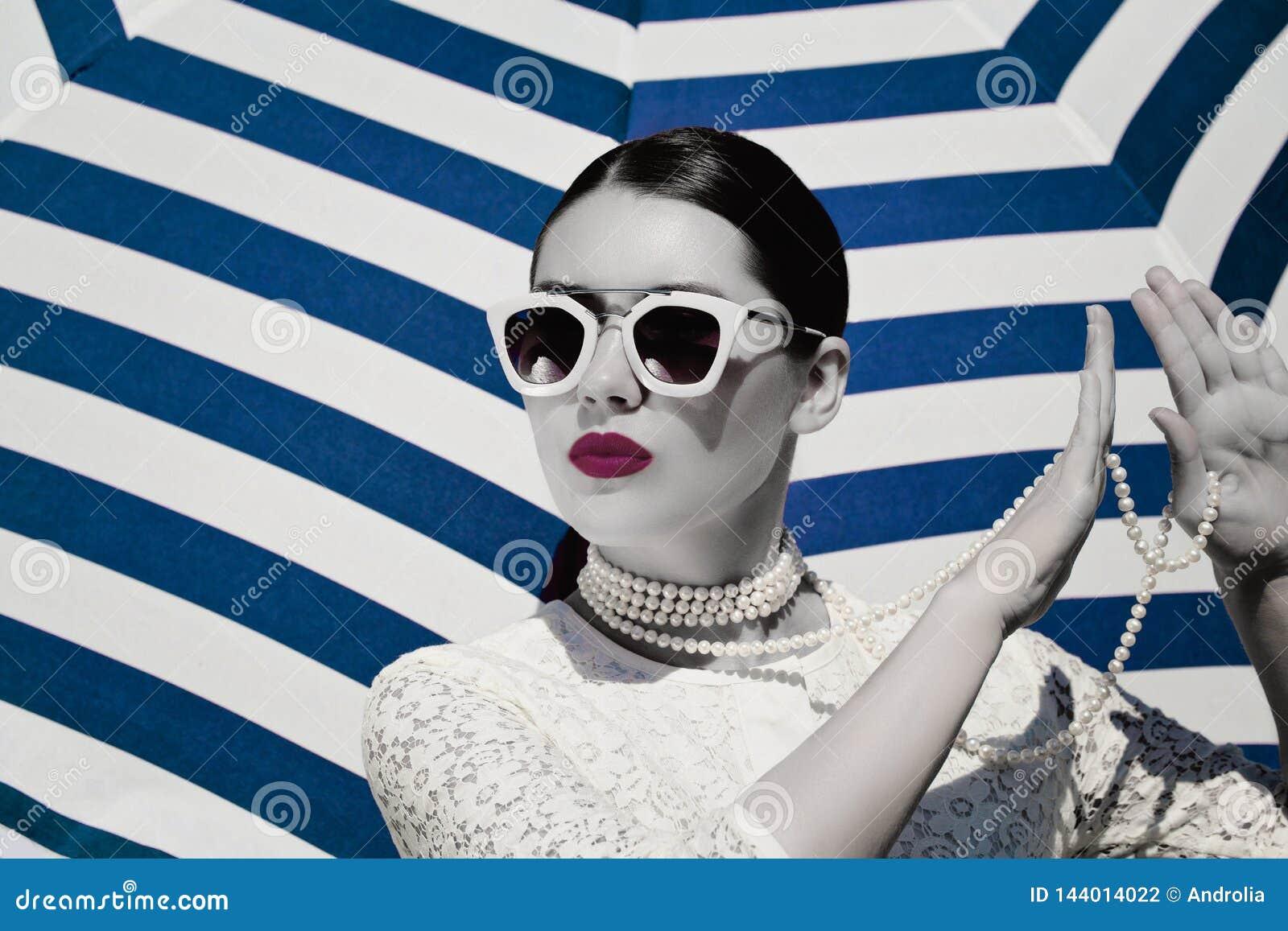 Ritratto di una giovane donna graziosa in vestito bianco dal pizzo, collana bianca della perla ed occhiali da sole rosa-chiaro