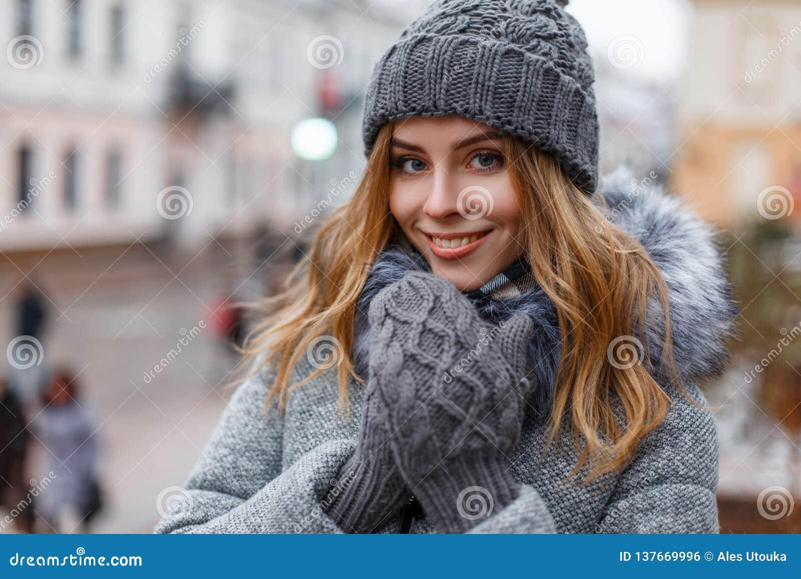 Ritratto di una giovane donna meravigliosa con i bei occhi azzurri con trucco naturale in un sorriso dolce in un cappello tricott