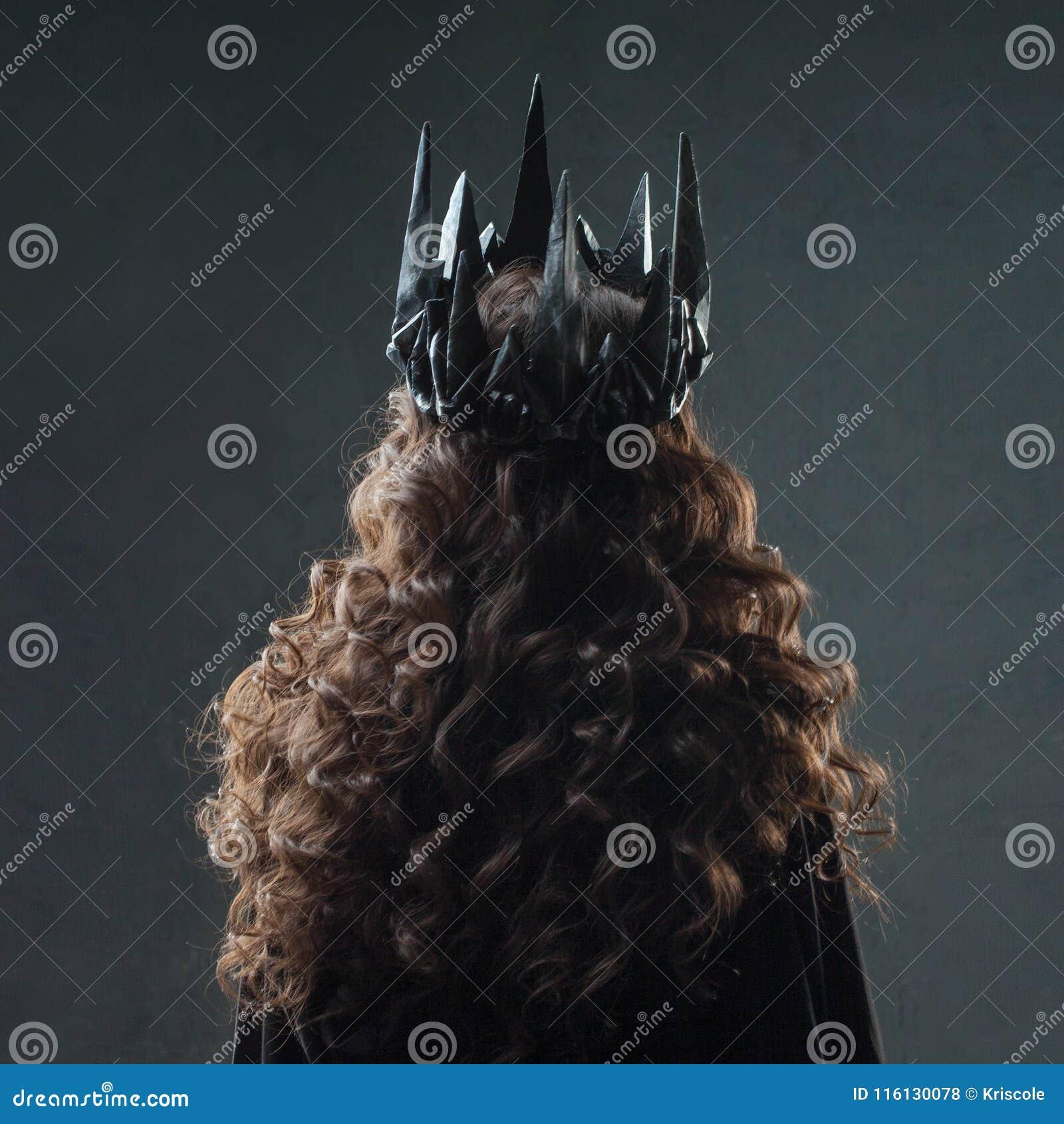 Ritratto di una principessa gotica Bella giovane donna castana in corona del metallo e mantello nero