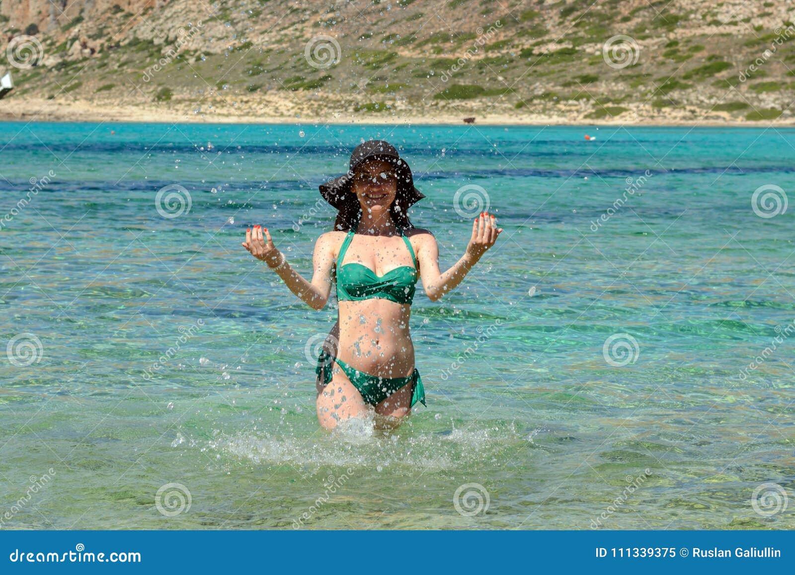 Ritratto di una ragazza allegra in un costume da bagno black hat e