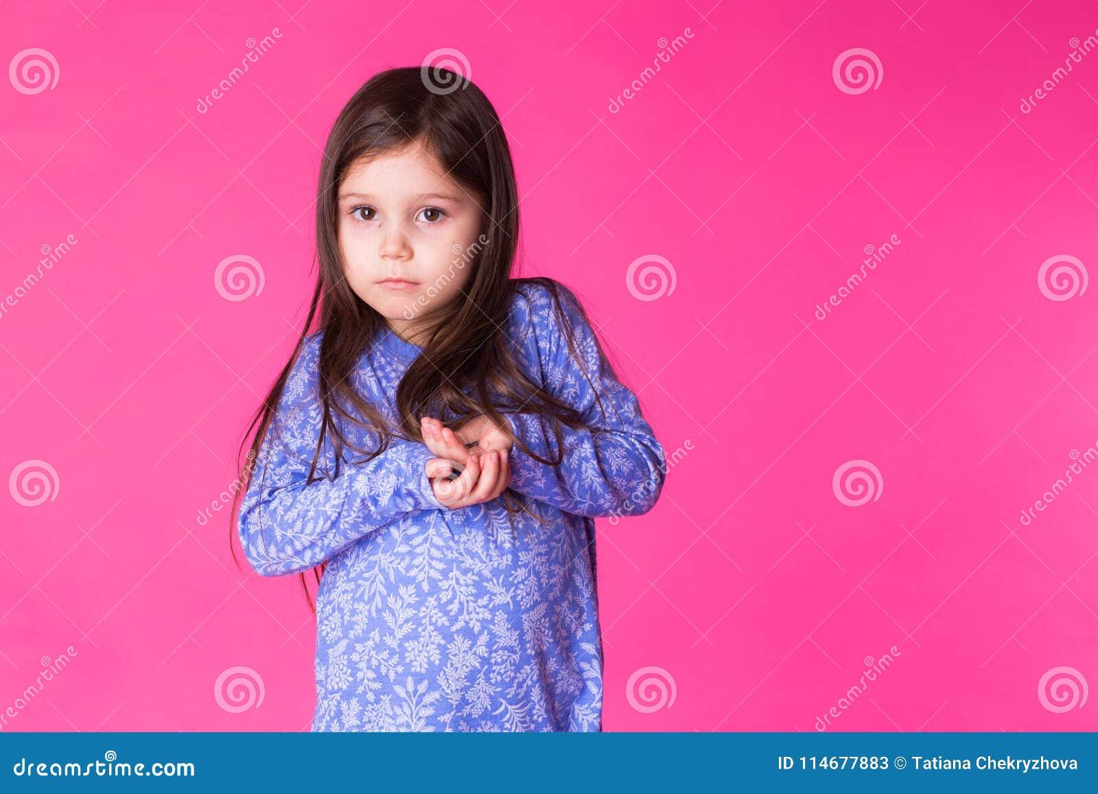 Ritratto di una ragazza castana affascinante del piccolo bambino, isolato su fondo rosa