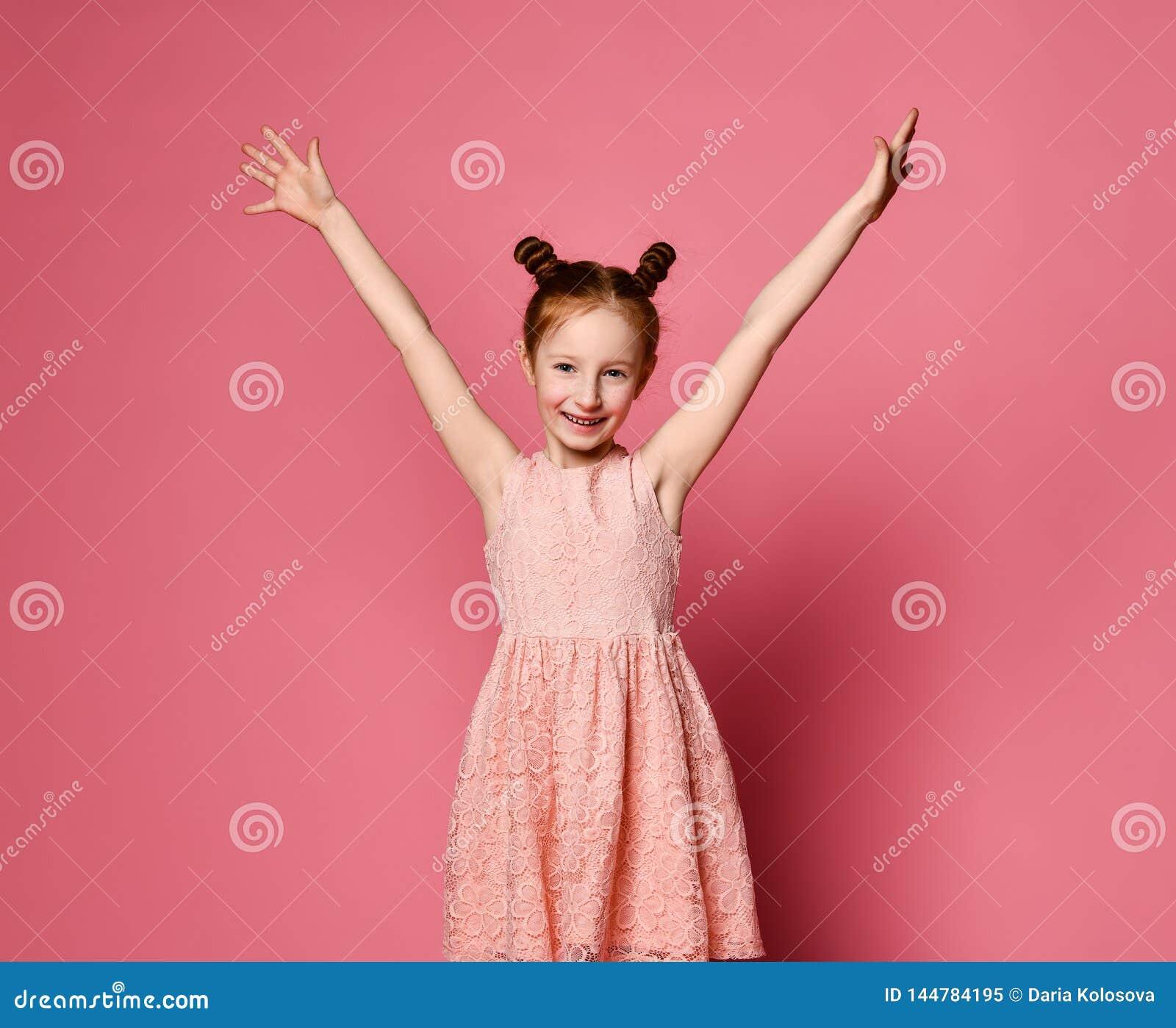 Ritratto di una ragazza con capelli rossi che sorride alla macchina fotografica con le mani nell aria