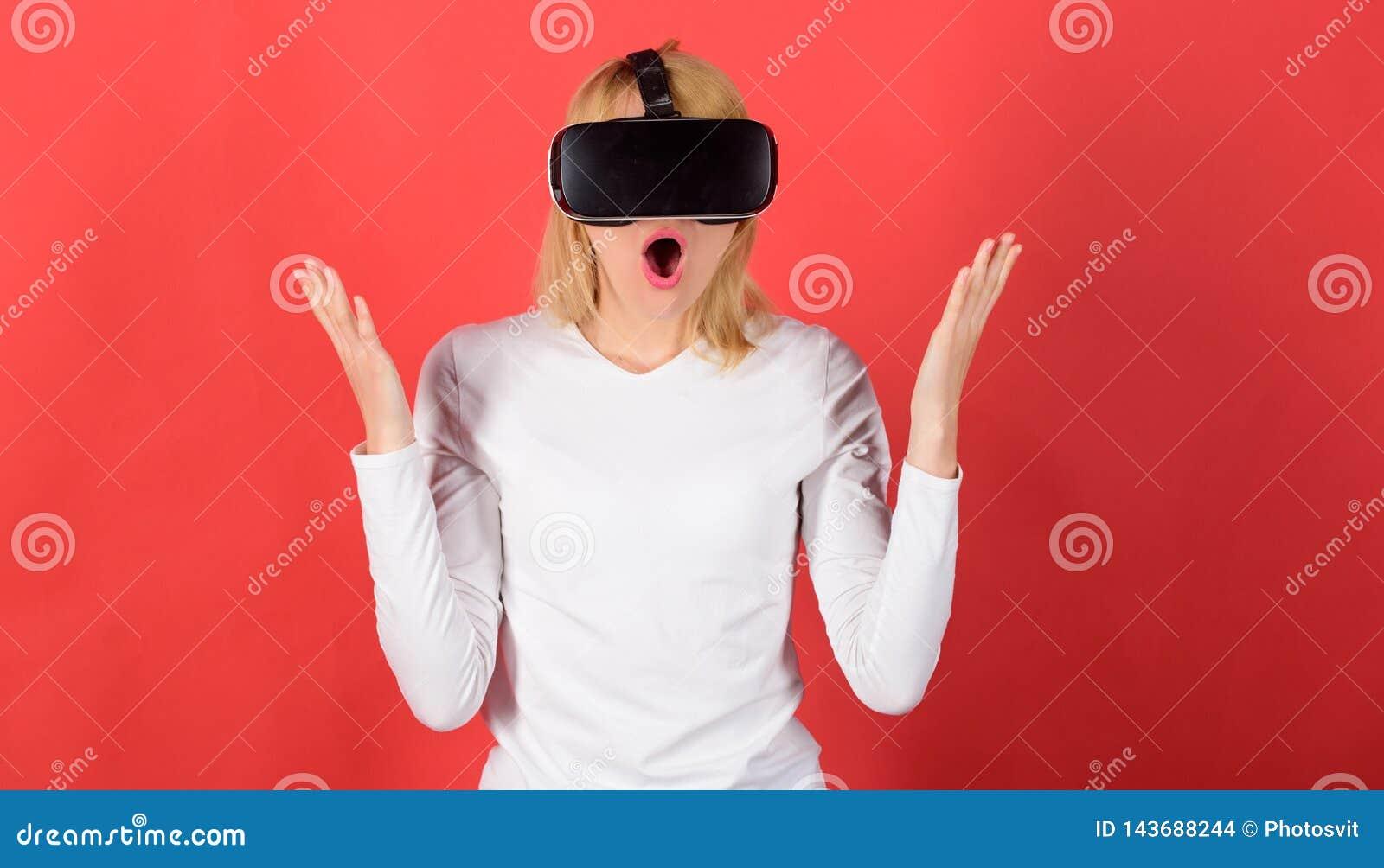 Ritratto di una ragazza stupita che per mezzo di una cuffia avricolare di realtà virtuale isolata su fondo rosso Persona con real
