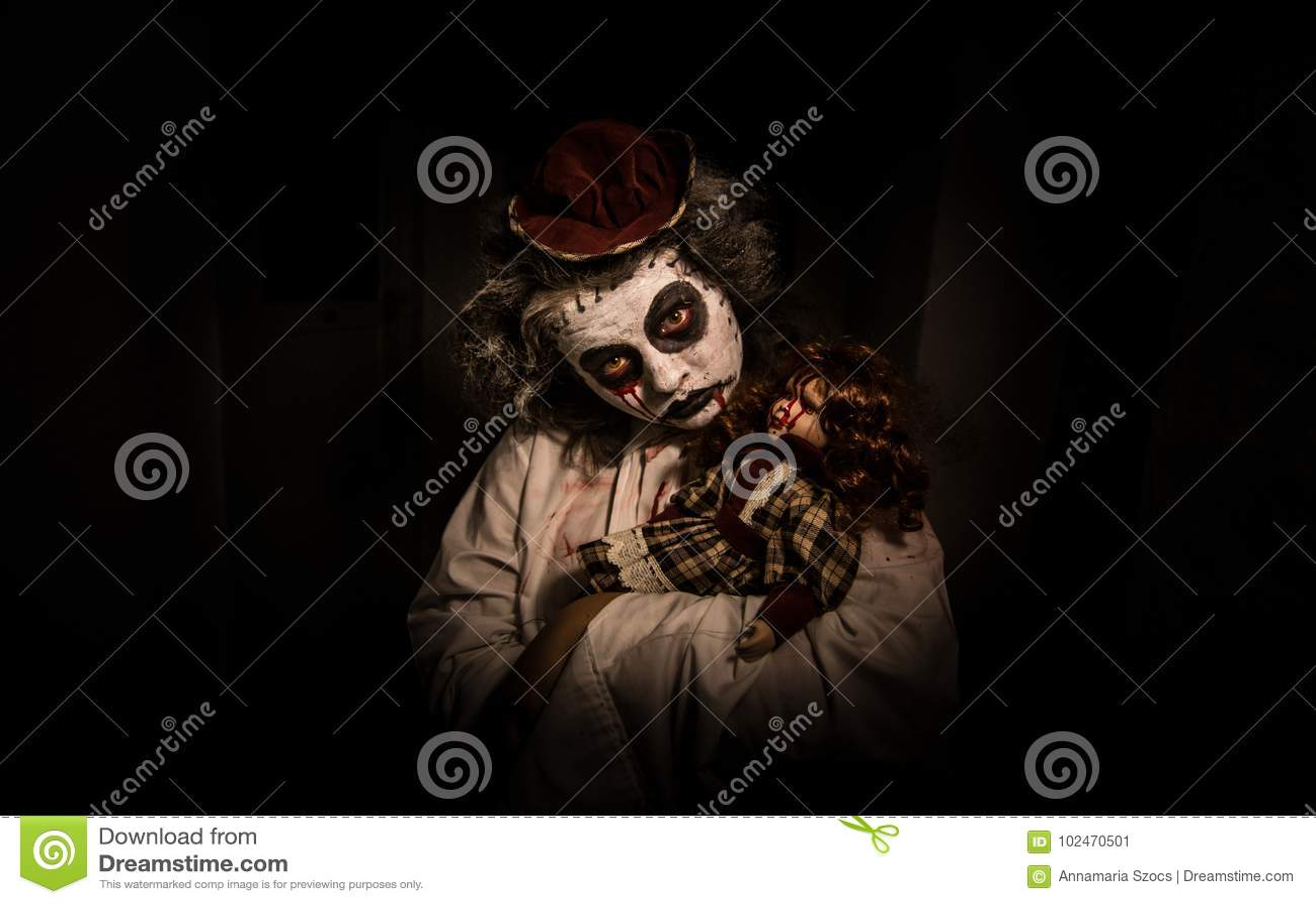 Ritratto di una ragazza terrificante con la bambola sanguinosa