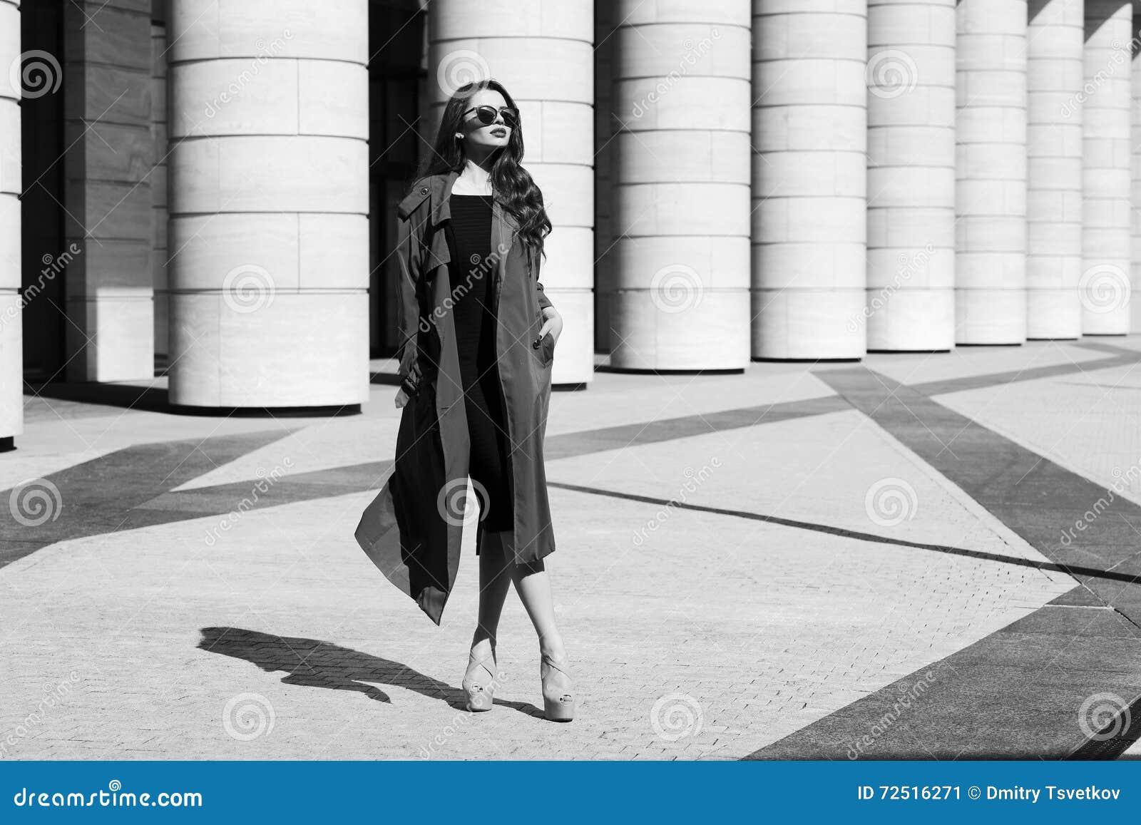 87eaad84ab41 Adatti a stile di moda il ritratto dinamico di giovane bella donna graziosa  che posa alla via della città in vestito nero