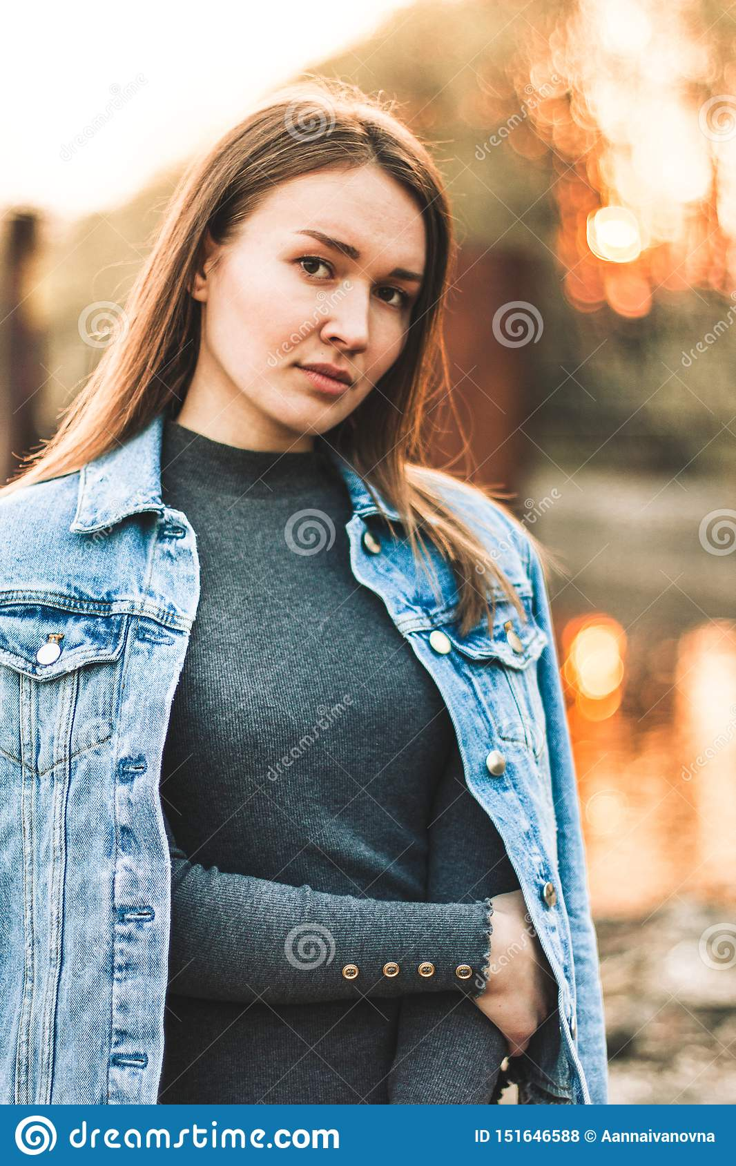 Ritratto giovane della ragazza bionda caucasica attraente, snella, bella in un rivestimento dei jeans La ragazza sorridente gode