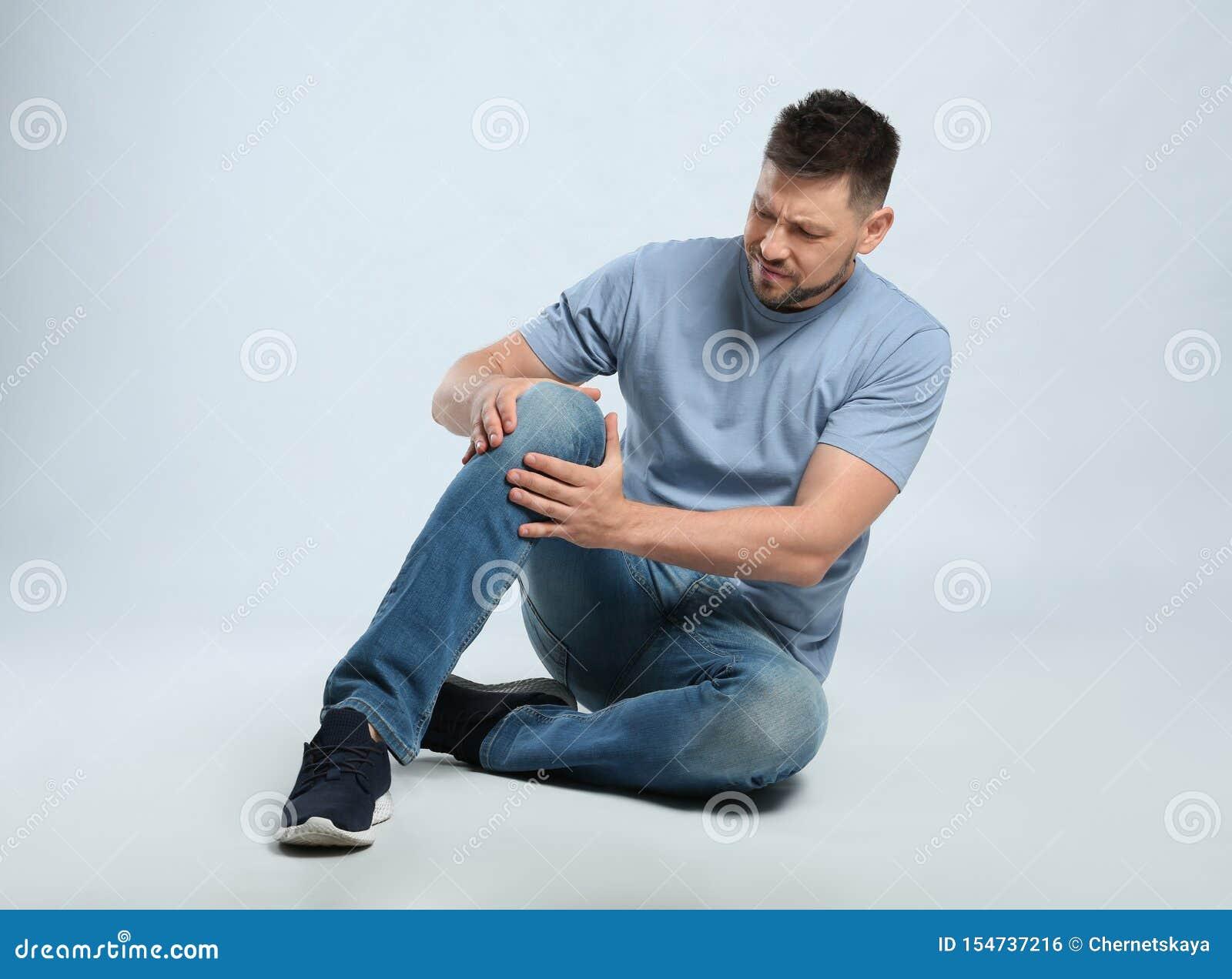 Ritratto integrale dell uomo con i problemi del ginocchio che si siedono su grigio