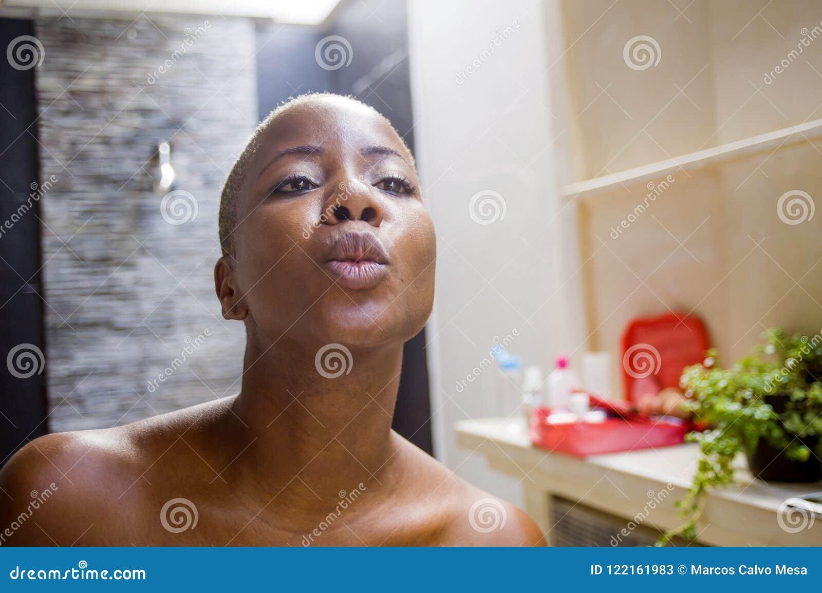 Ritratto naturale di stile di vita di giovane bagno afroamericano nero attraente e felice della donna a casa che esamina specchio