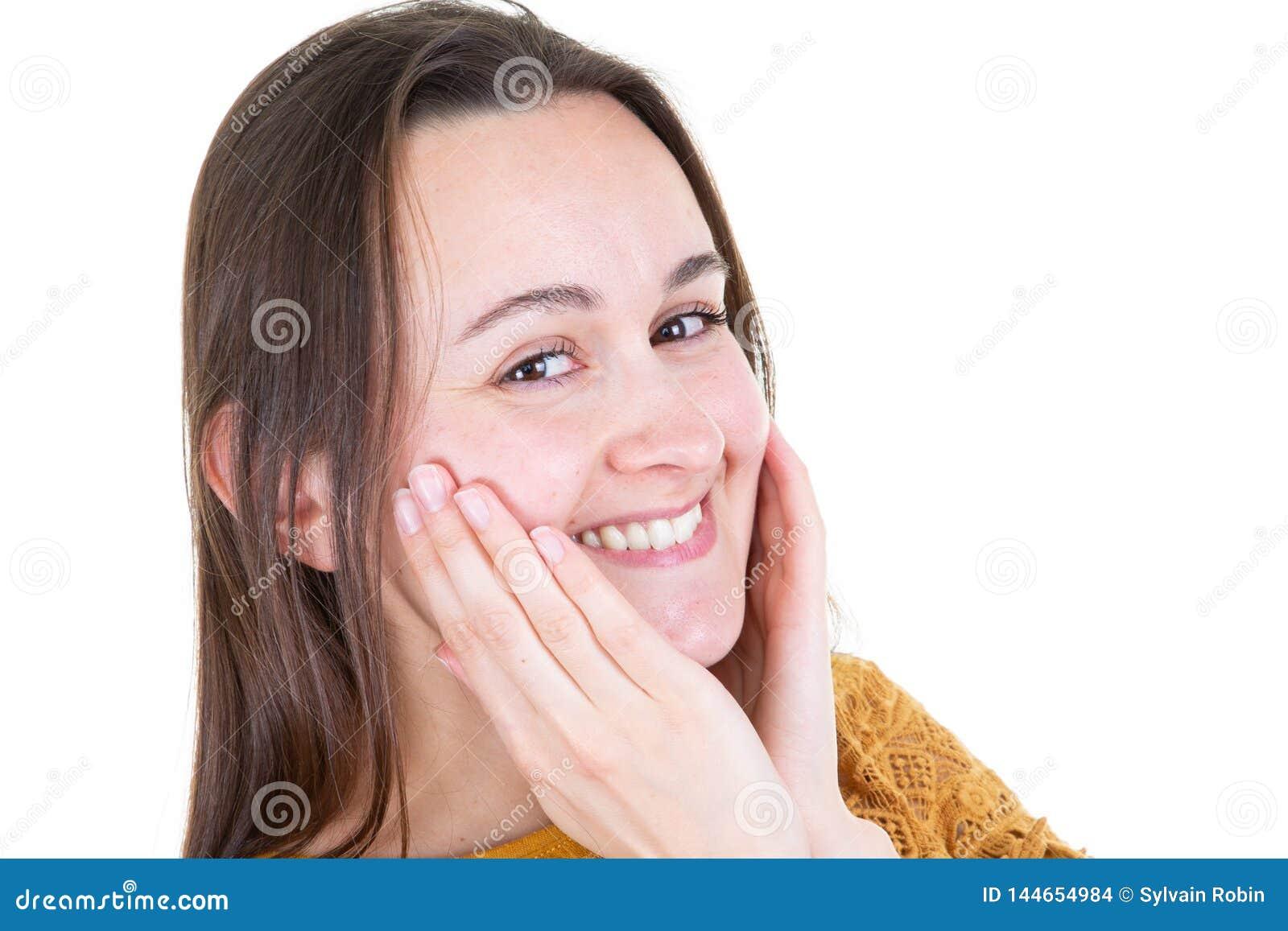 Ritratto orizzontale del sorriso sveglio della giovane donna che si tiene per mano sotto il mento che sembra femmina allegra graz