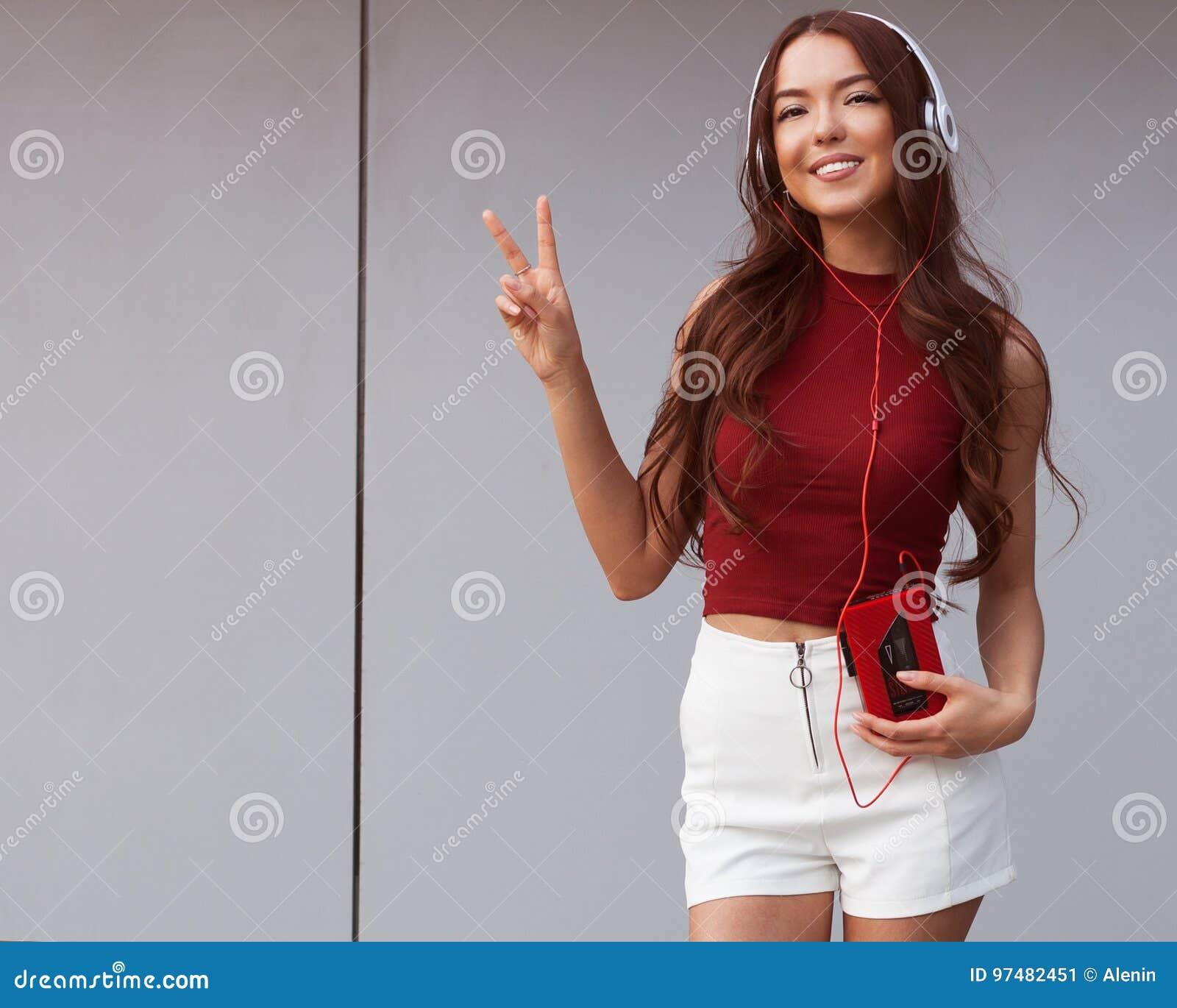 Ritratto soleggiato di una ragazza asiatica in un agrostide bianco e negli shorts bianchi, cuffie e con una posa d annata del gir