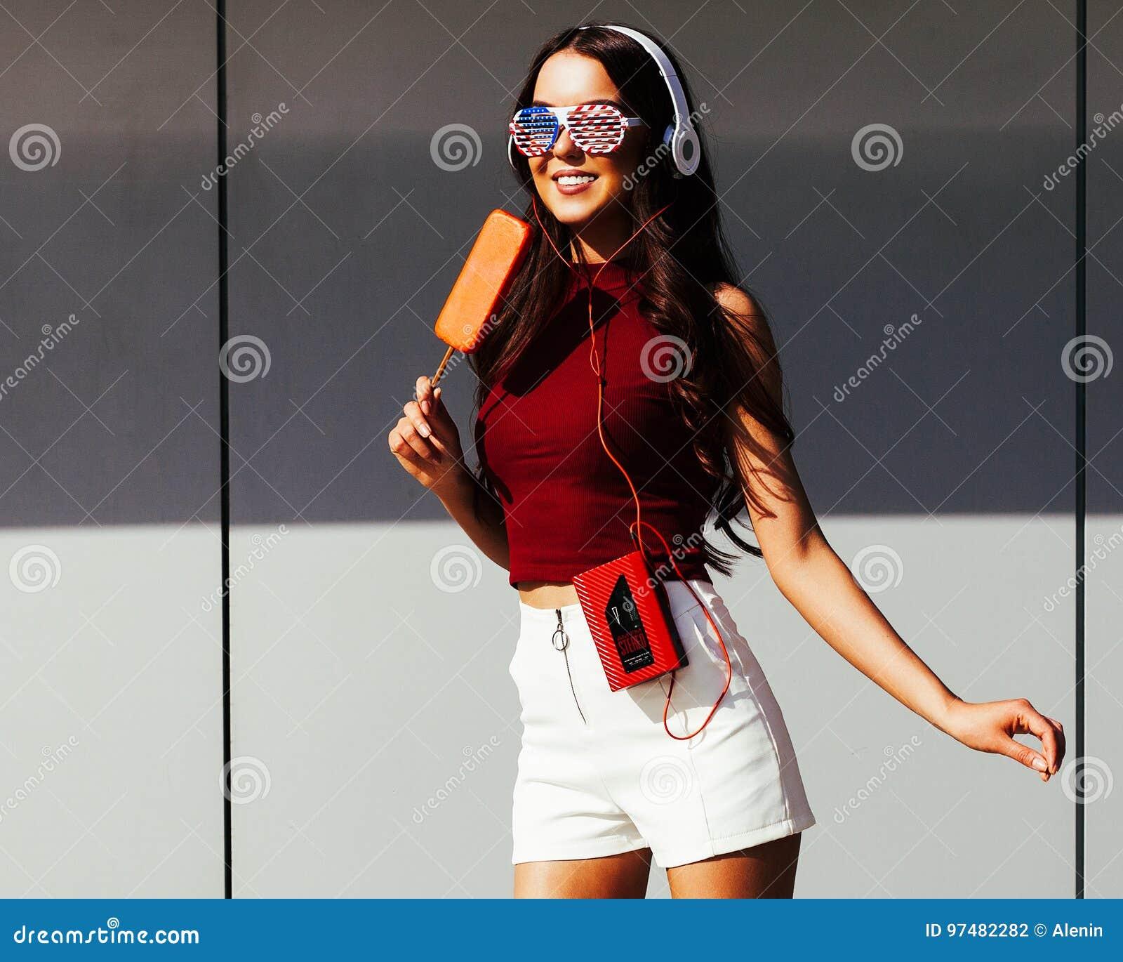 Ritratto soleggiato di una ragazza asiatica in un attrezzatura d avanguardia di estate, nelle cuffie, negli occhiali da sole alla