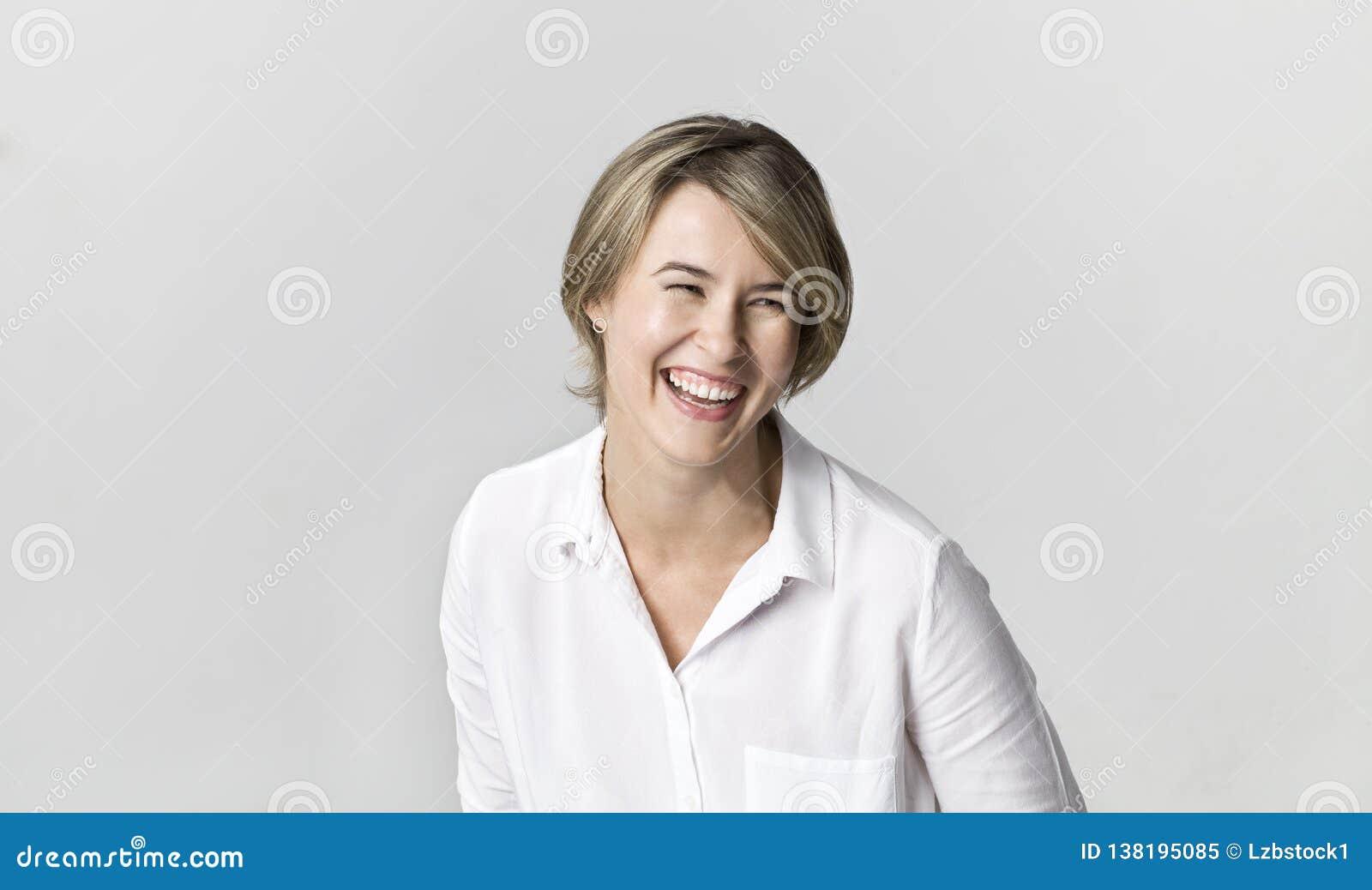 Ritratto sorridente d uso della camicia bianca giovane della donna bionda espressiva e molto felice