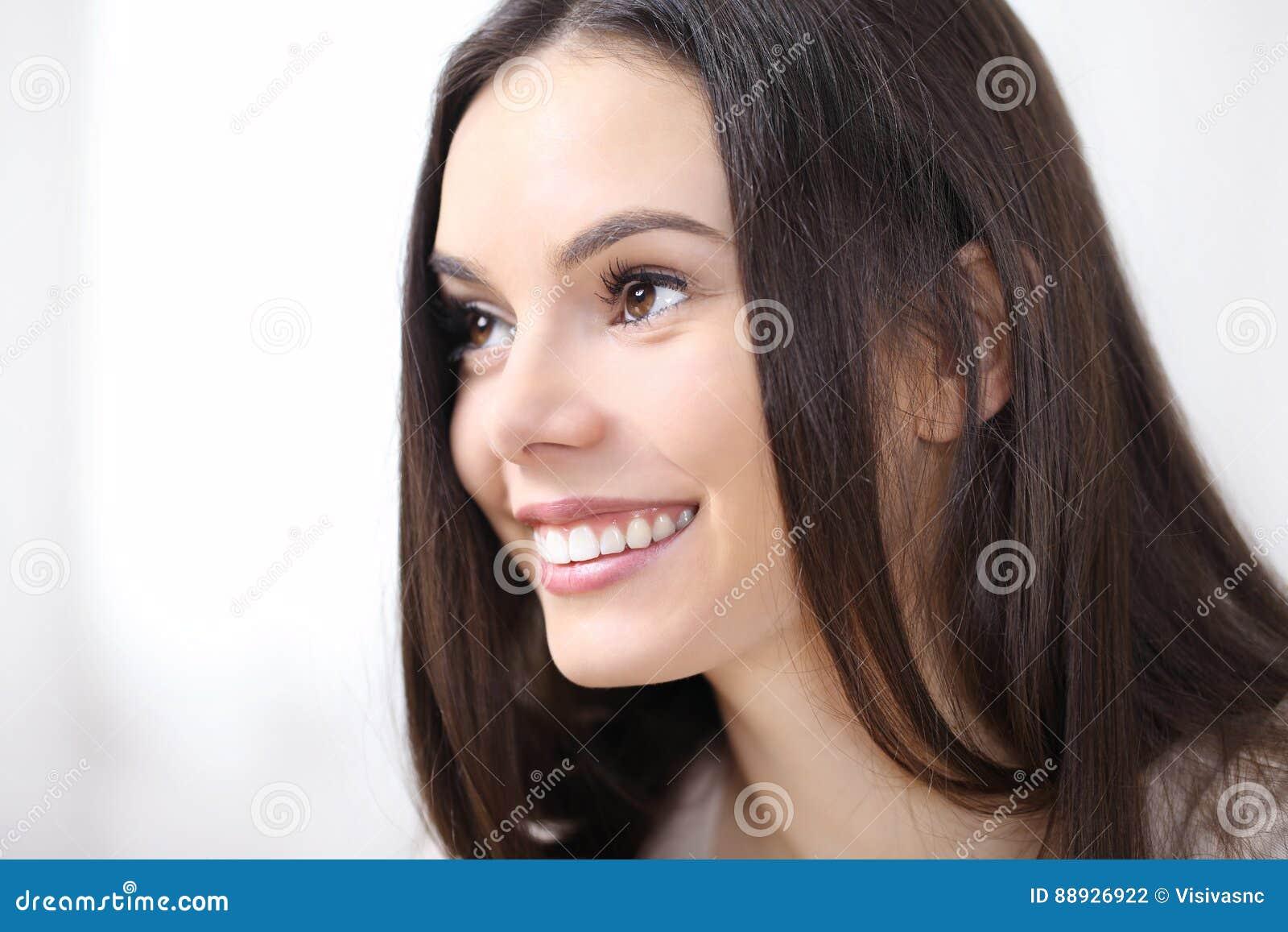 Ritratto sorridente della donna nello sguardo di profilo, isolato su bianco