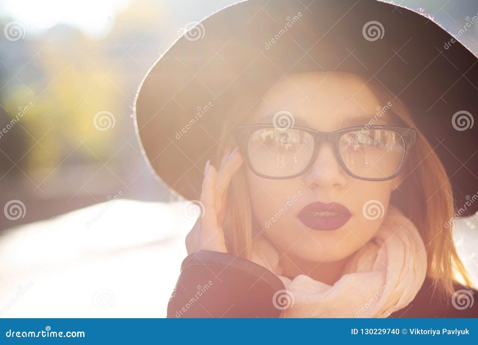 Ritratto urbano del modello biondo adorabile con le labbra rosse che indossano i glas