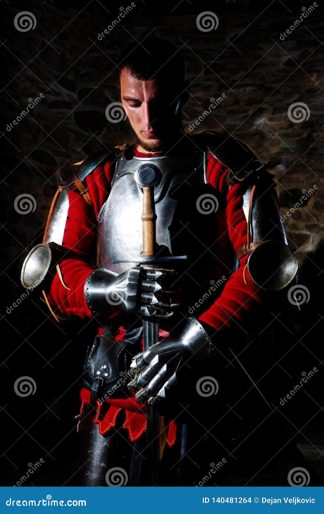 Ritter-Standing With Metal-Klinge und mit dem Kopf gebeugt im Gebet