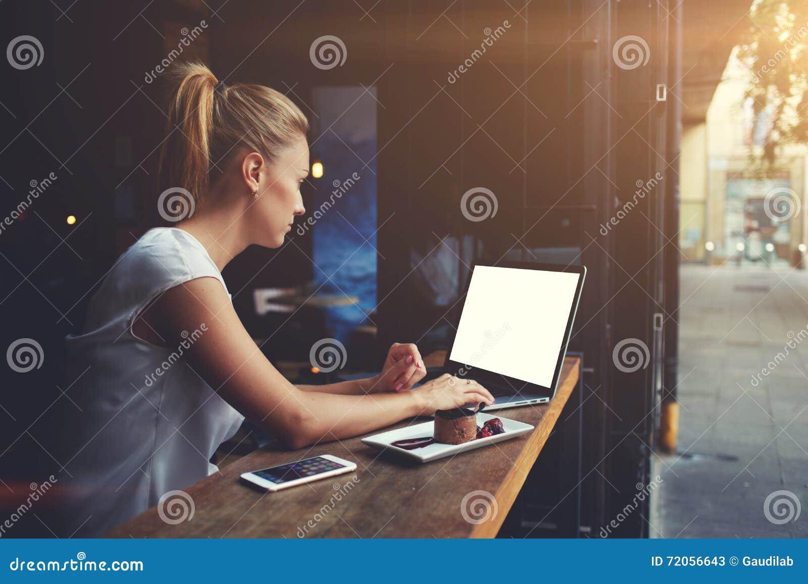 Riuscite free lance della donna sveglia che utilizzano computer portatile mentre sedendosi nella caffetteria