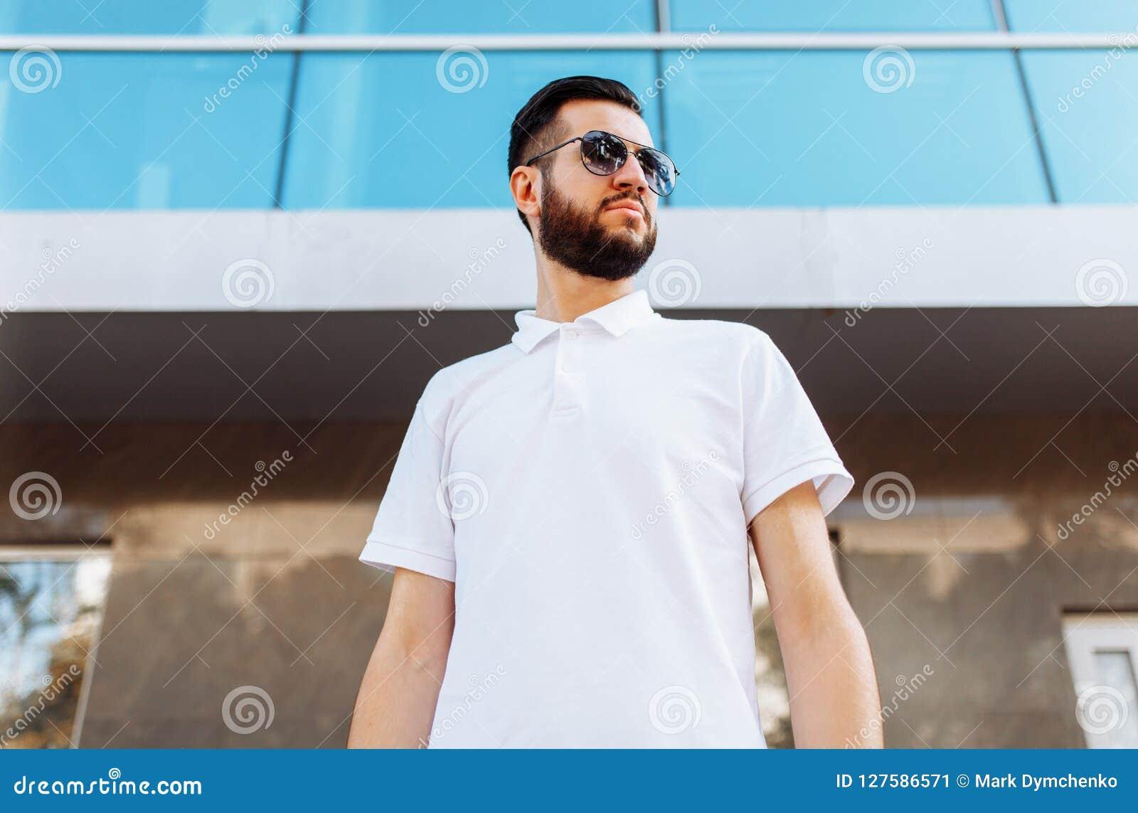 2688c0ce0deb8a Pantaloni a vita bassa alla moda in camicia bianca nei precedenti della  costruzione di vetro