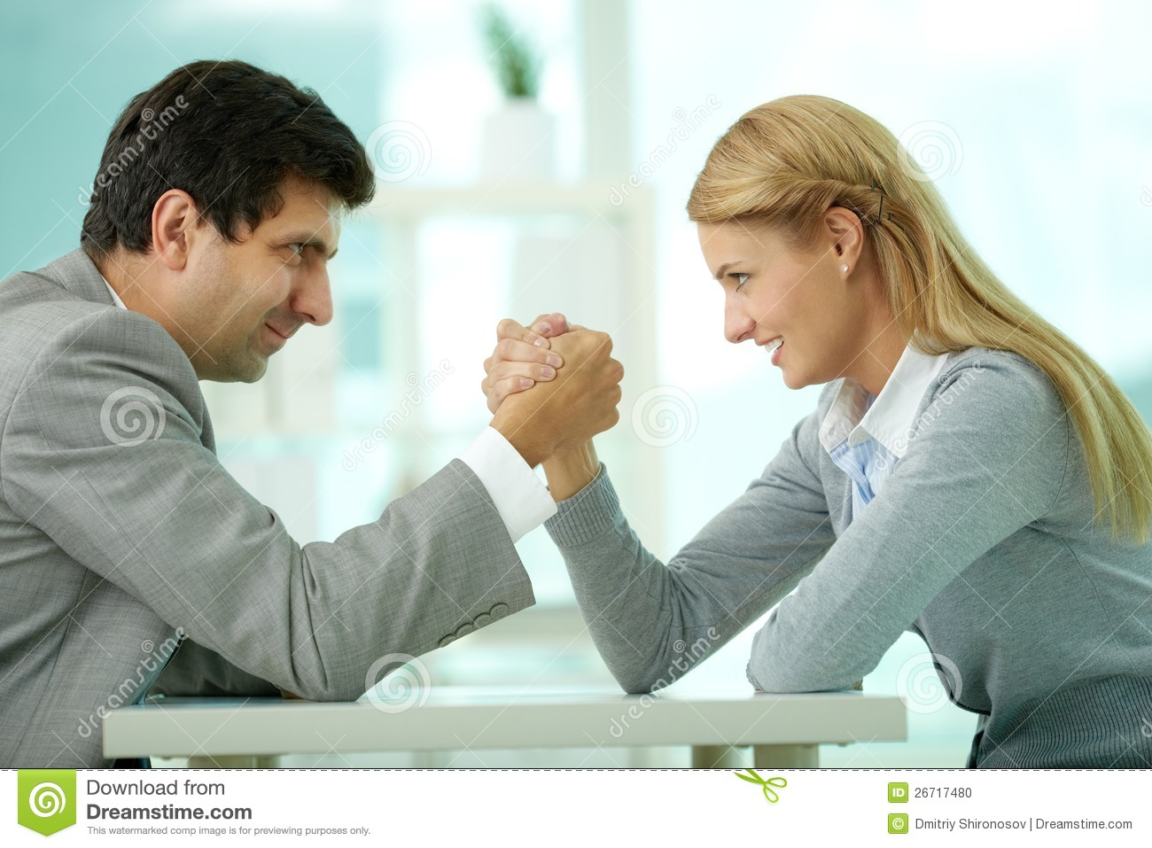... and women in arm wrestling gesture on working table during meeting