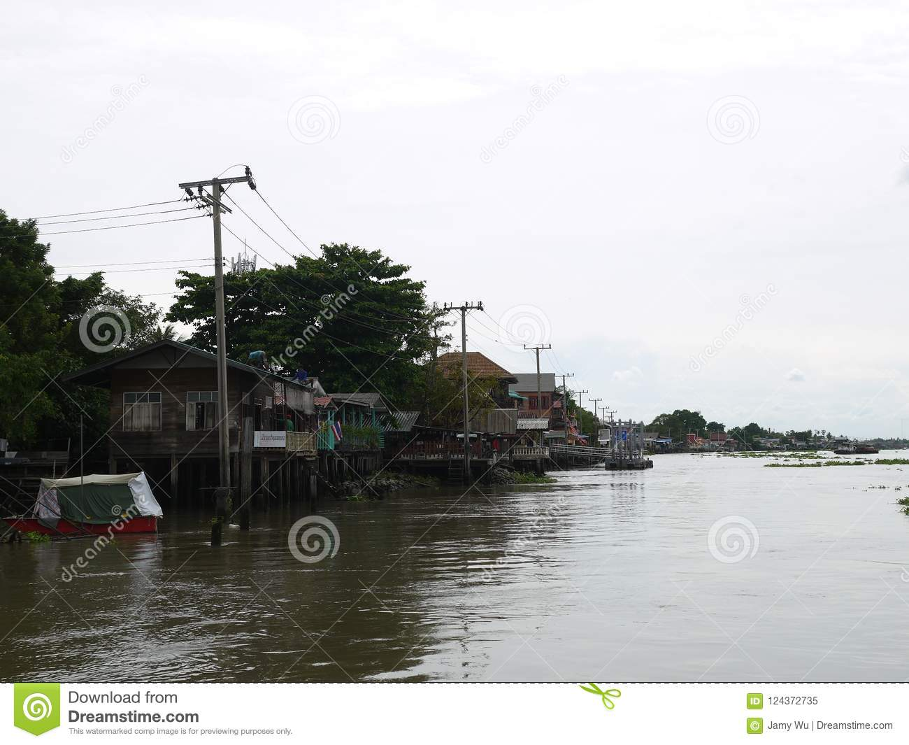 Chaophya river ecology life in the bright sunshine day, community of waterside wooden houses, temples, and parking boats.