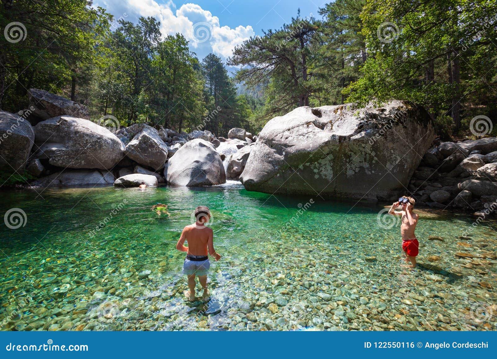 River in a natural landscape, some children inside water.