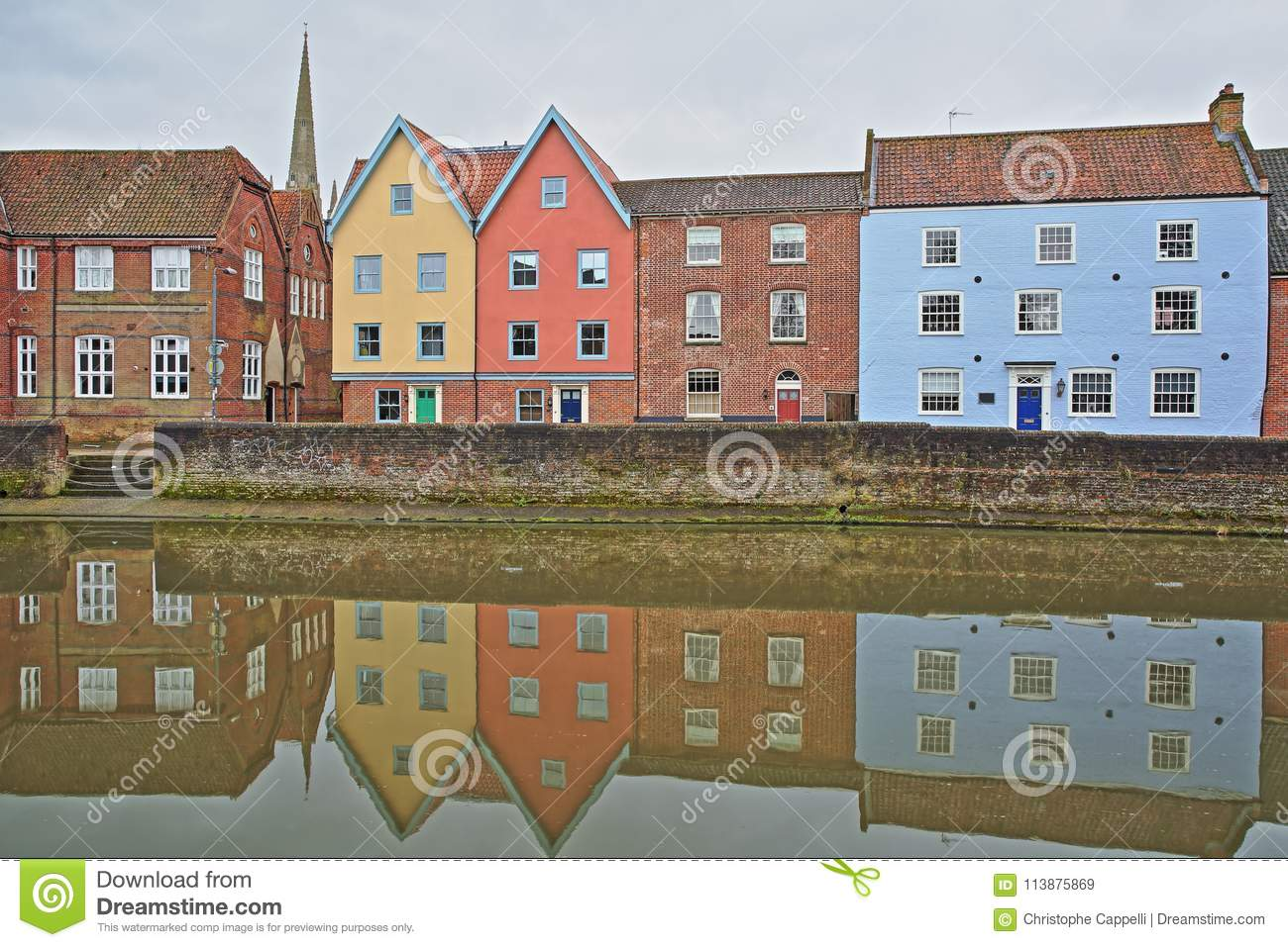 The riverside river Wensum with reflections of colorful houses and the tower and spire of the Cathedral