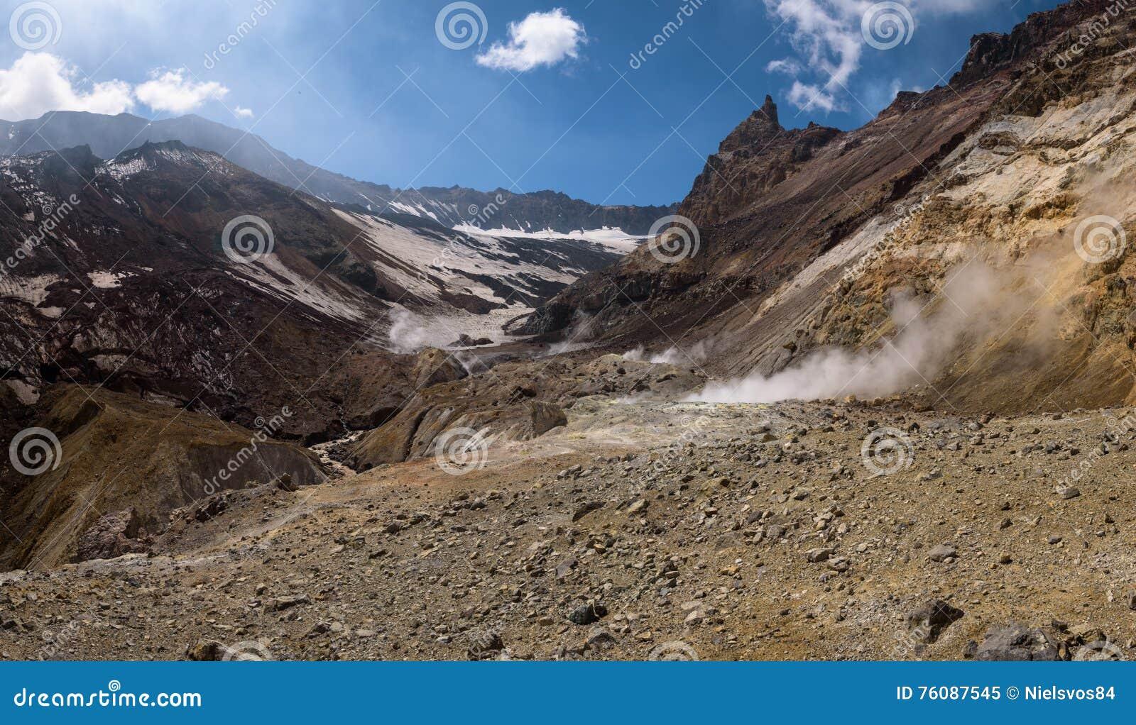 Rivière traversant le canyon avec des fumerolles à l intérieur de cratère de volcan de Mutnovsky