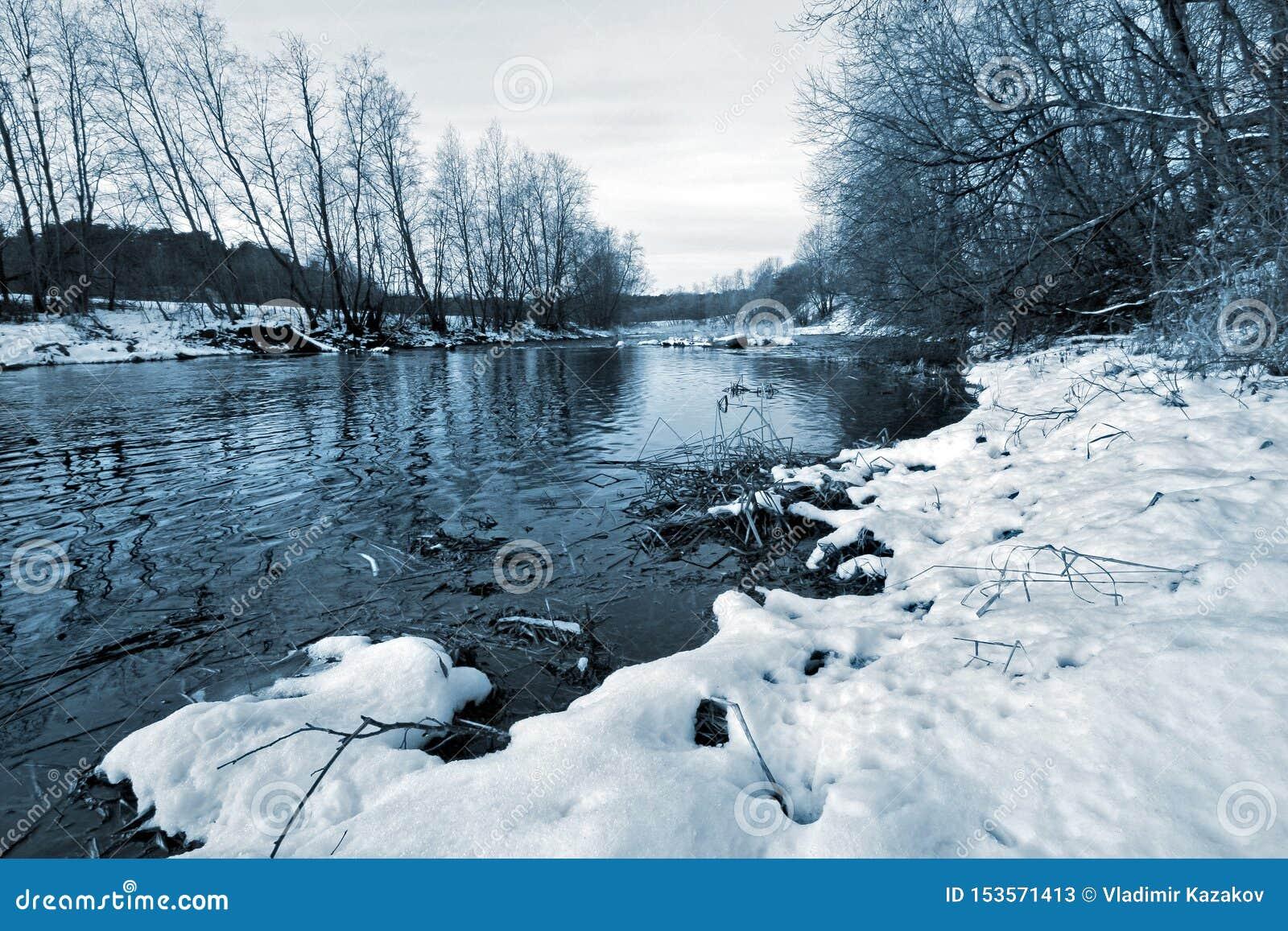 Rivier zonder ijs in de winter met sneeuw op de kust en het groeien bomen