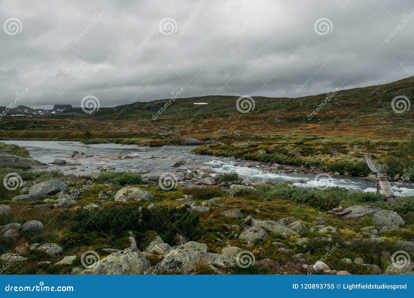 Rivierstroom die door stenen en heuvels op gebied, Noorwegen, Hardangervidda gaan