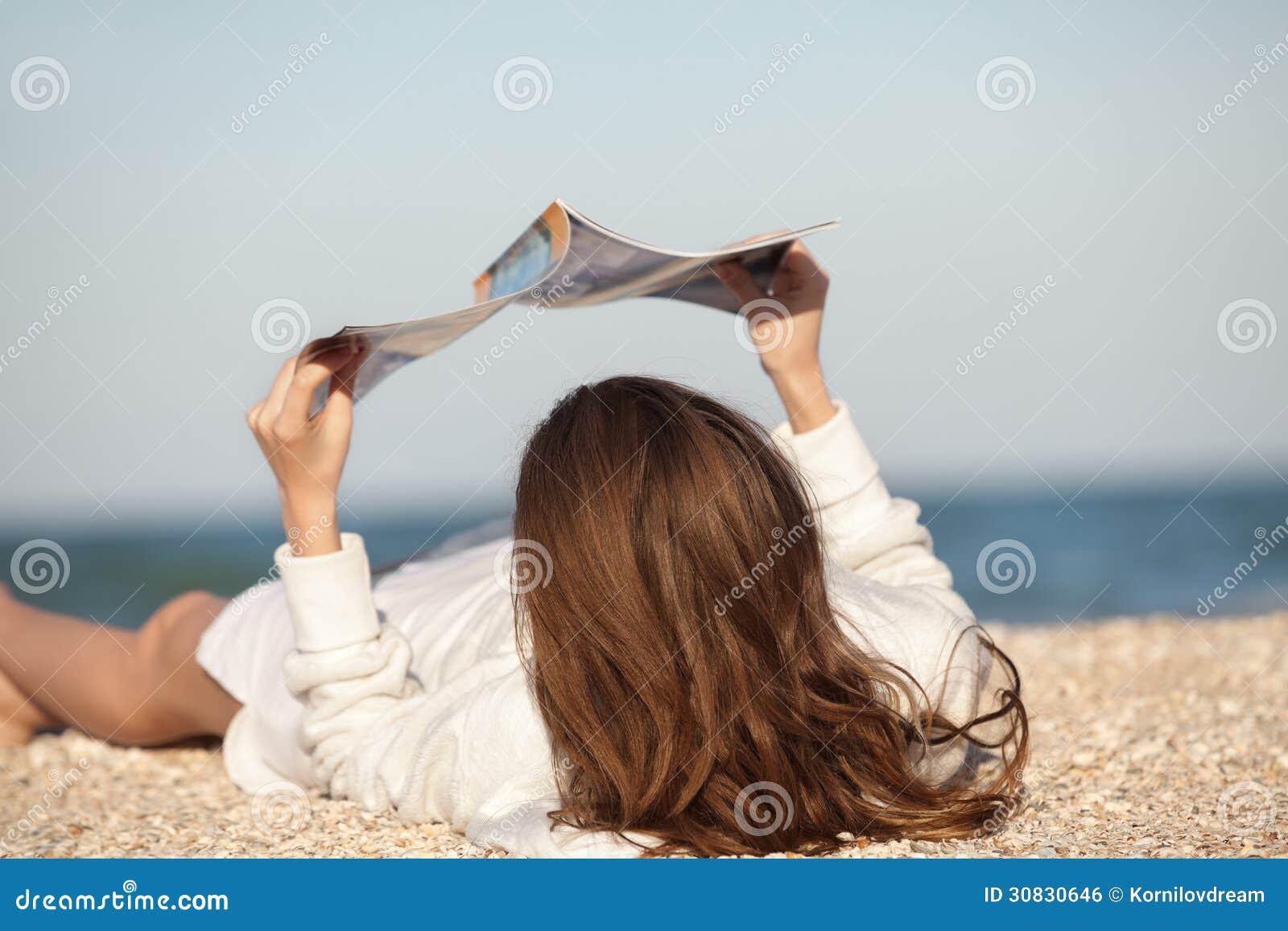 Rivista della lettura della donna sulla spiaggia