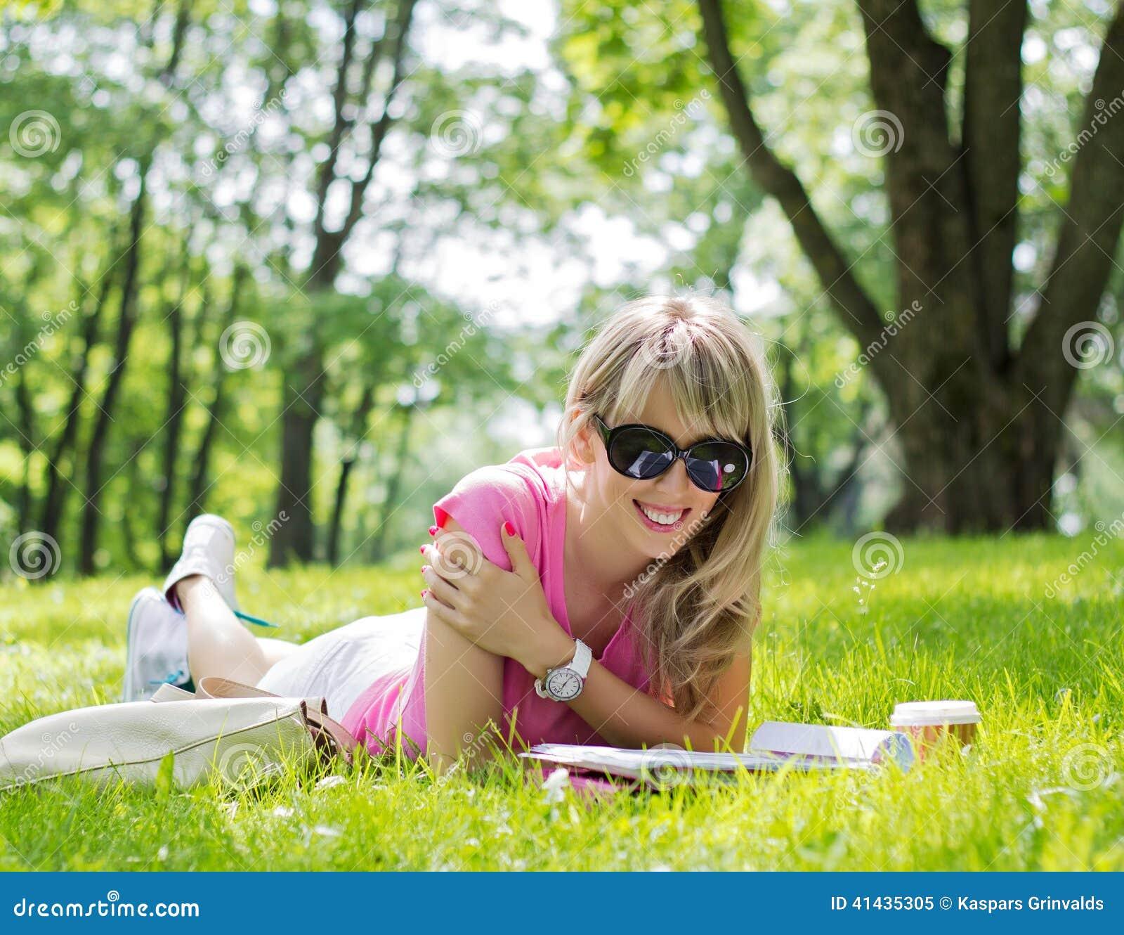 Rivista felice della lettura della giovane donna in parco