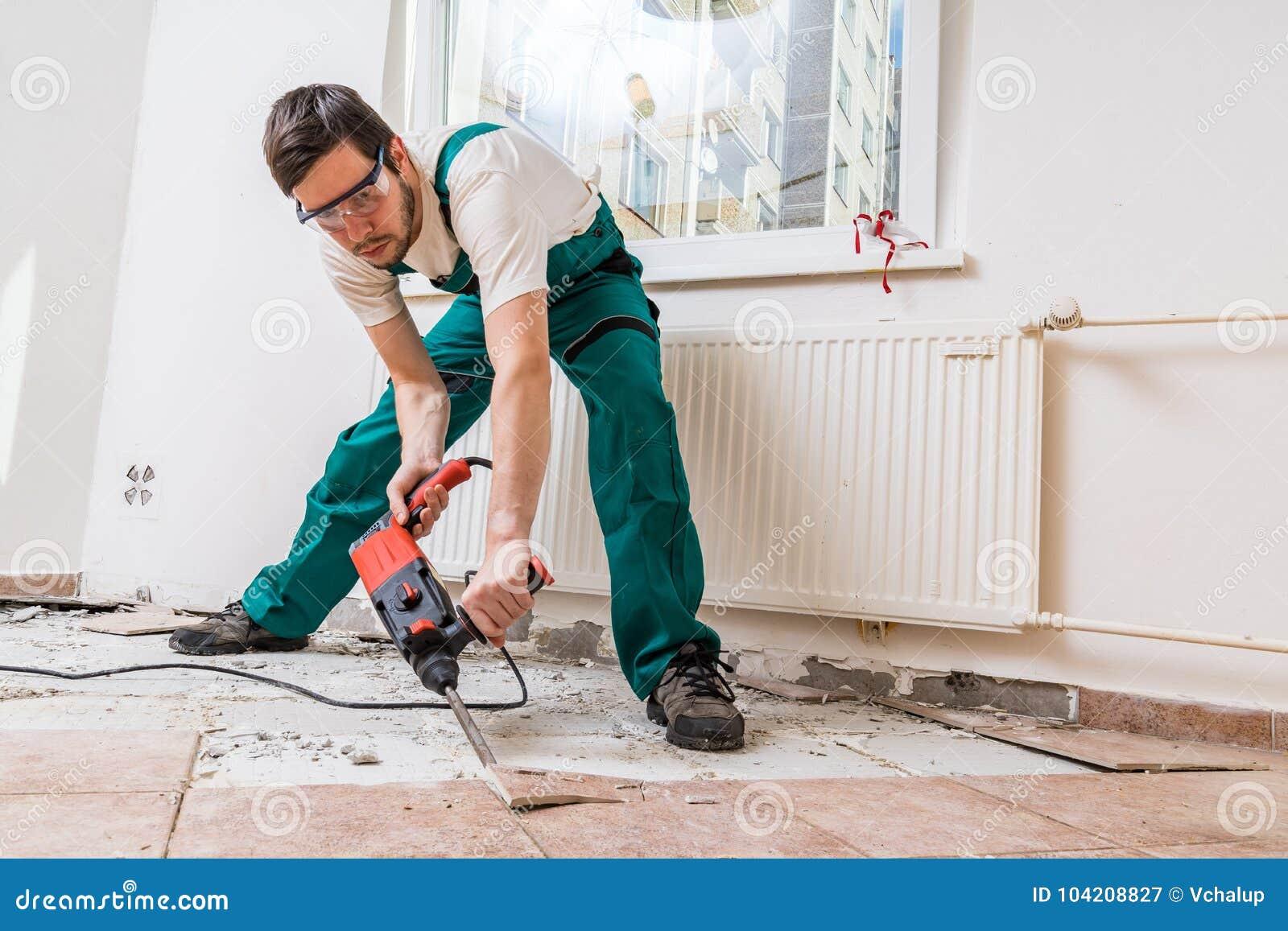 Rivning av gamla tegelplattor med tryckluftsborren Renovering av det gamla golvet