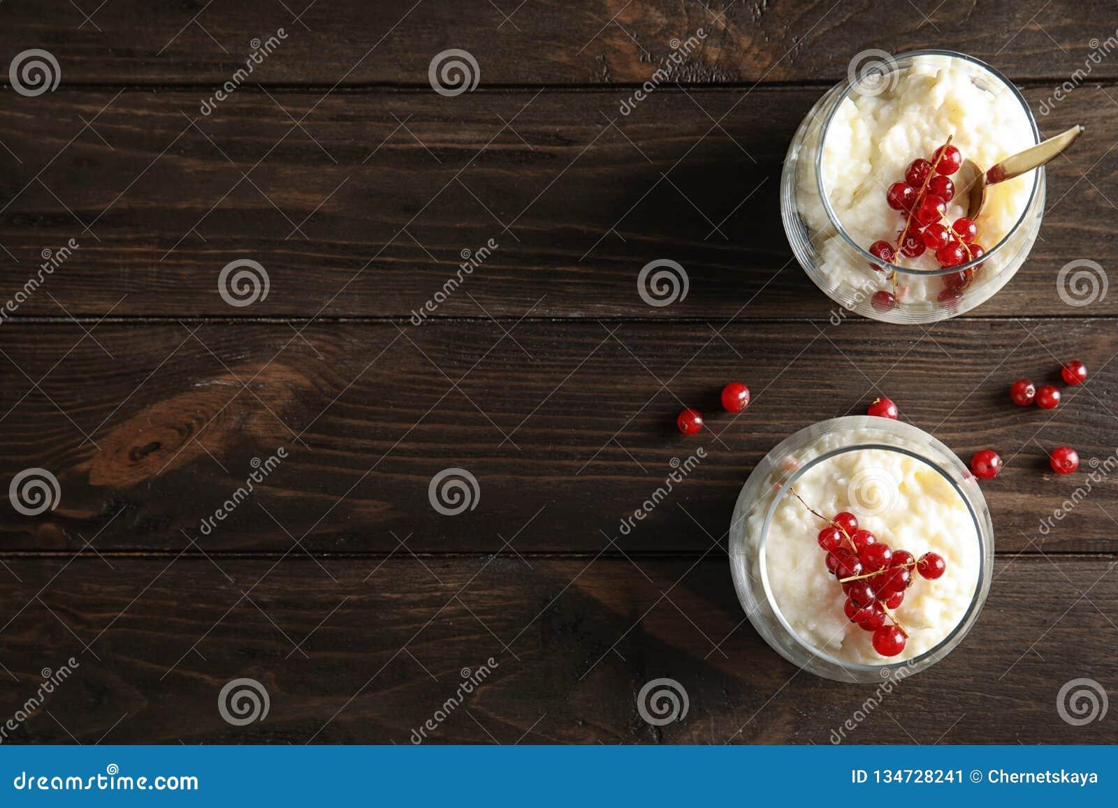 Riz au lait crémeux avec la groseille rouge dans les verres et les baies sur le fond en bois, vue supérieure