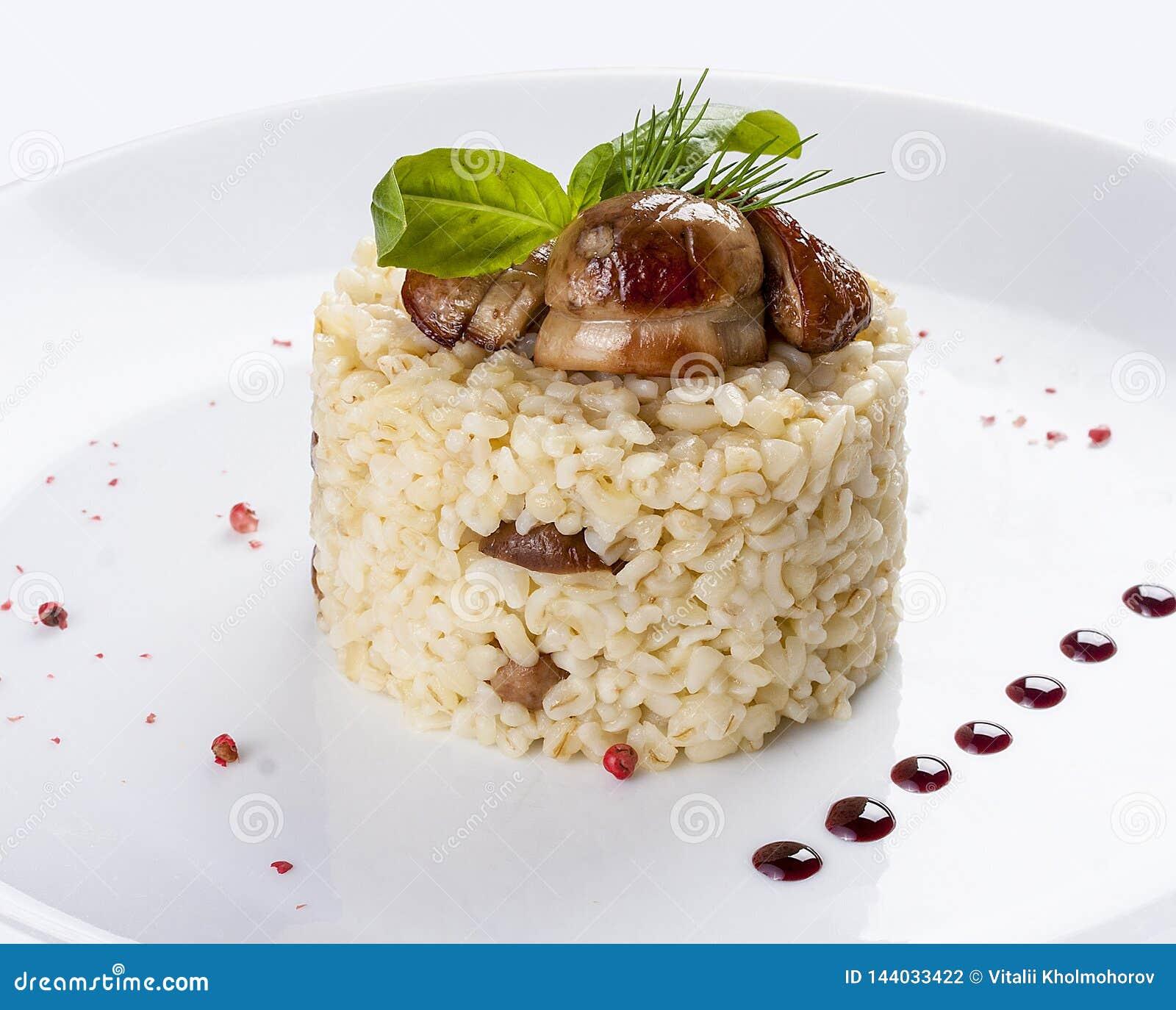 Riz avec des champignons de couche de porcini D un plat blanc
