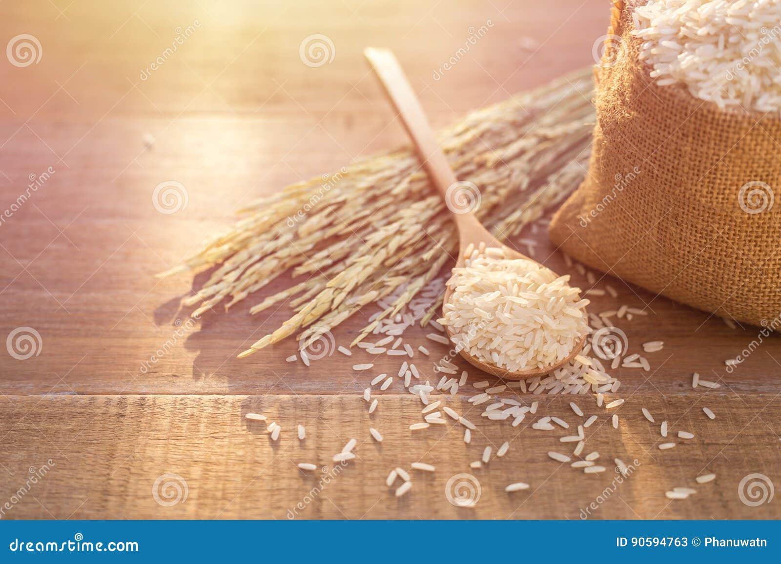 Riz thaïlandais de jasmin dans la cuillère et le petit sac sur le backgr en bois de table